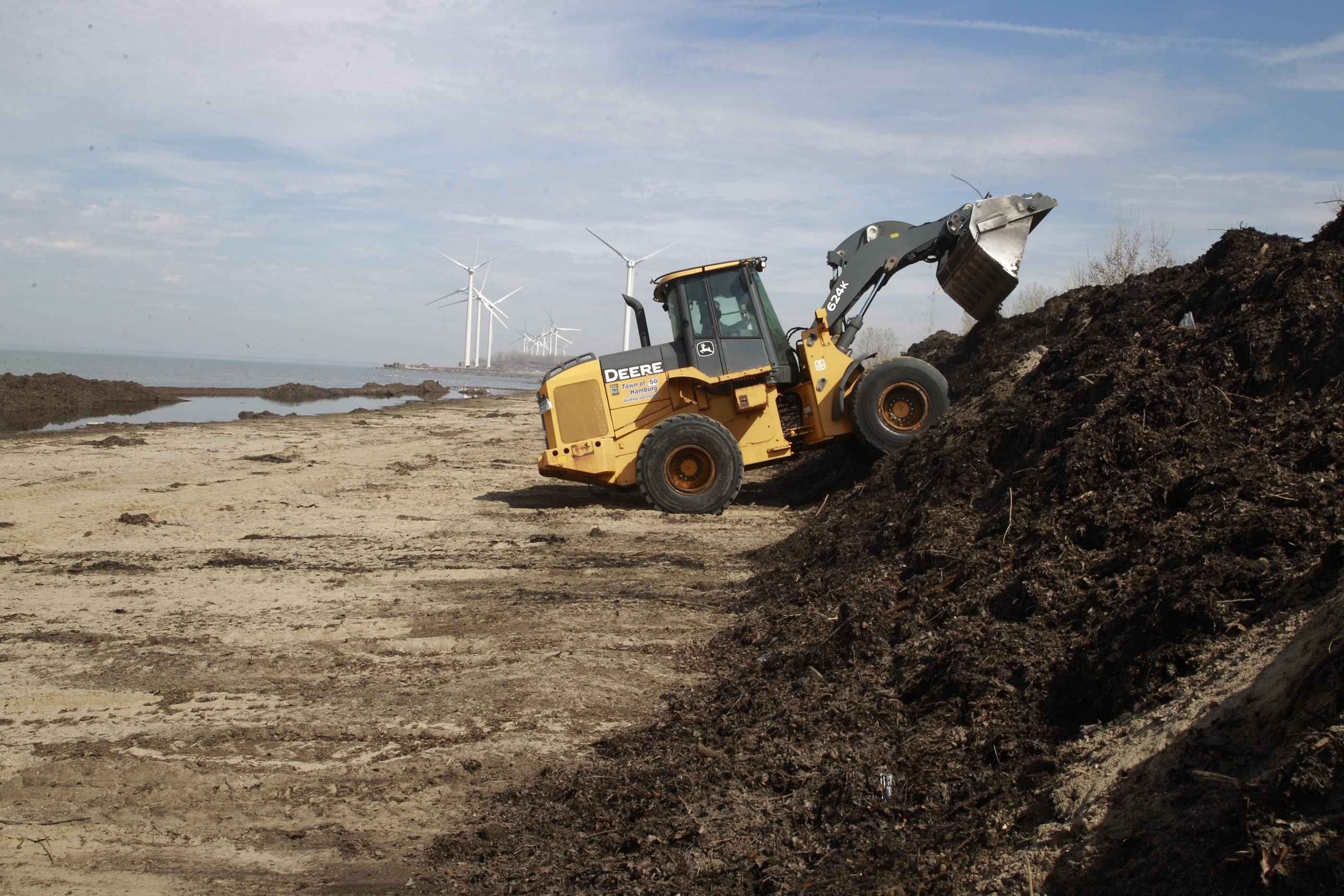 A front-end loader works on the task of cleaning Woodlawn Beach State Park which has been blocked off to vehicle traffic, due to the large amount of debris on the beach. (John Hickey/Buffalo News)
