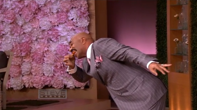 Steve Harvey demonstrates how to eat chicken wings on a date in response to a question from Buffalo. (Screenshot of video)
