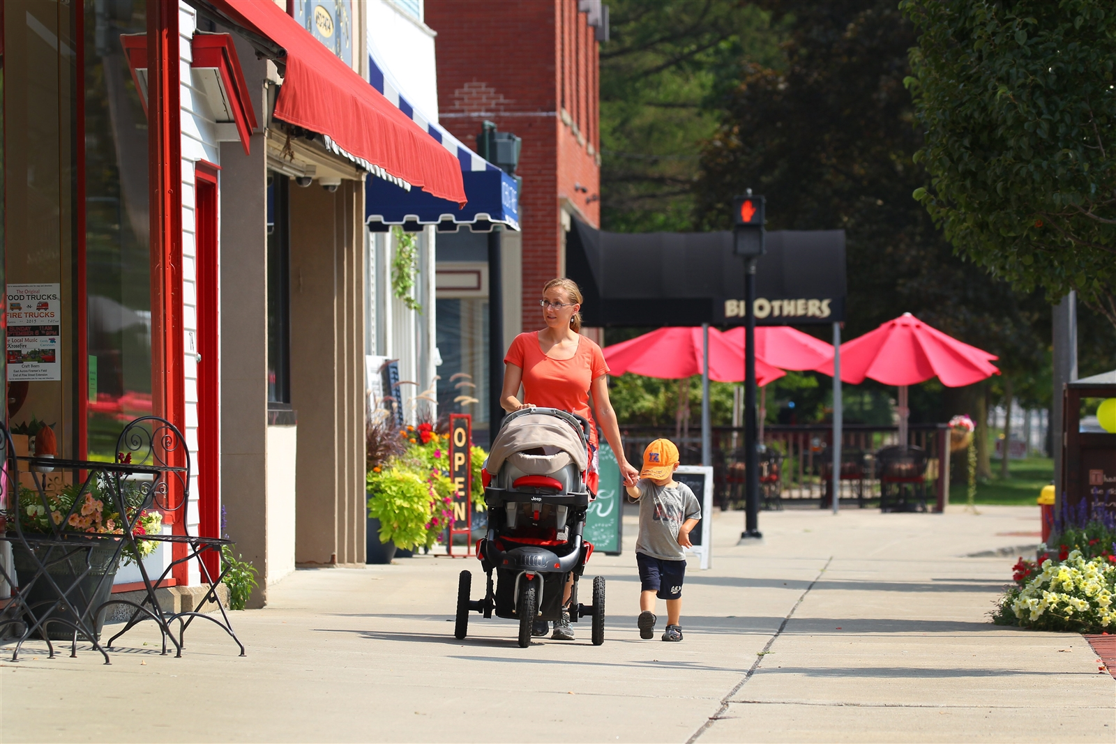 Danielle Cofta walks with her children Jackson, right, and Miles, in stroller, on Main Street in East Aurora.