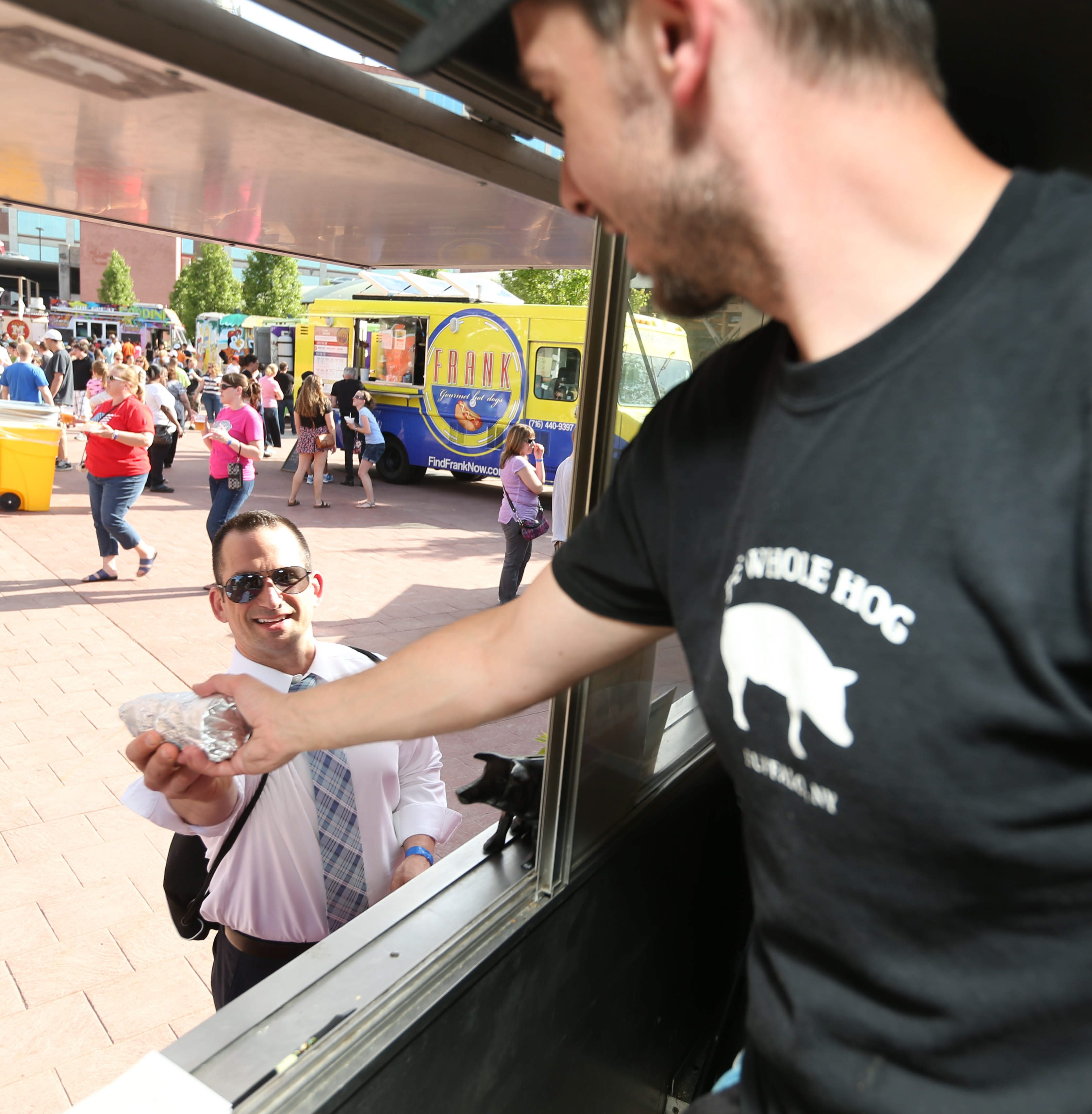 Matt Simpson, of Whole Hog food truck, hands an order to a customer at last week's Food Truck Tuesday at Larkinville.