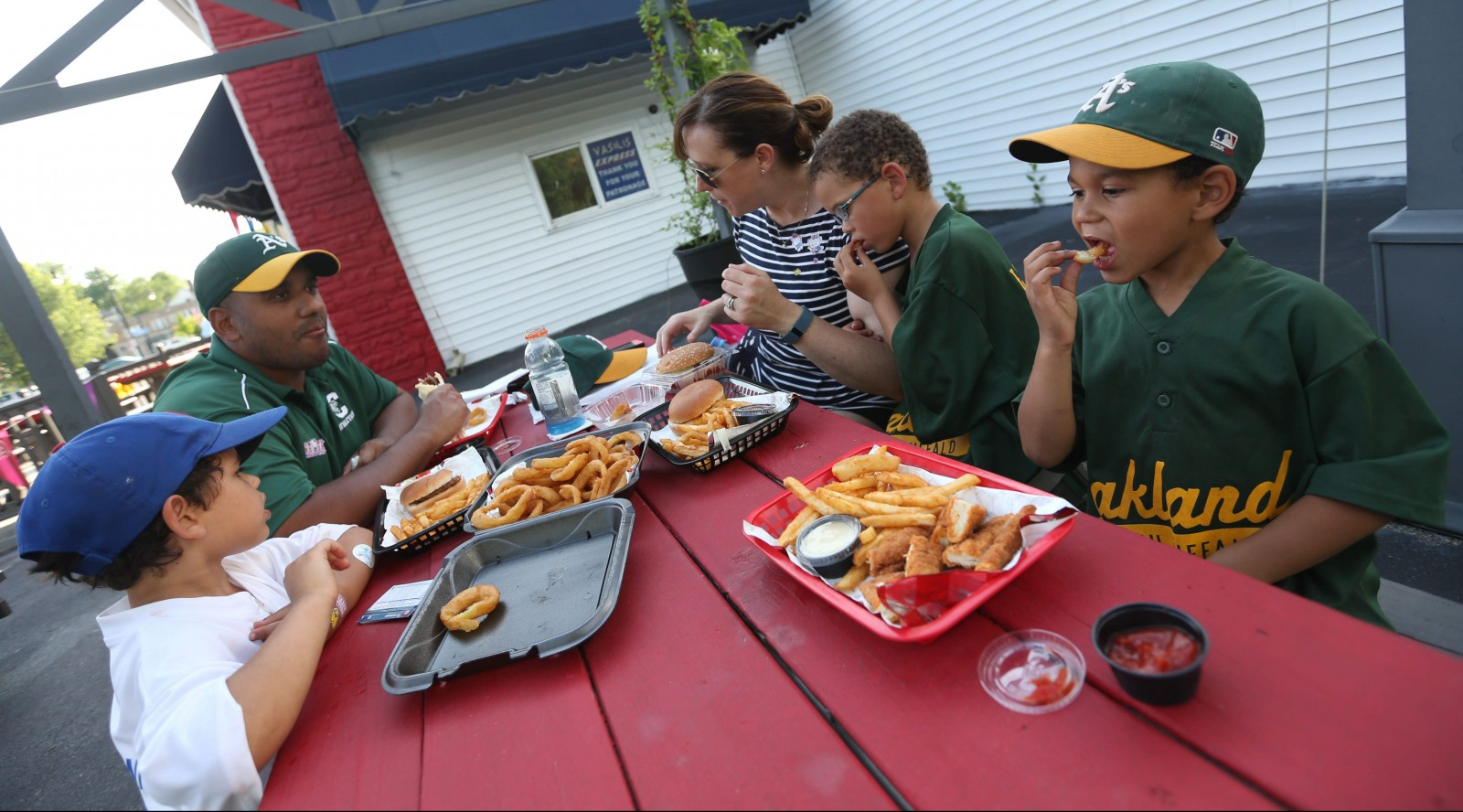 The Gomez Family enjoys dinner after their baseball game at Mighty Moe's on Hertel Avenue. From left are Eli, 4, Omar, Megan and twins Nate and Gabe, 6.