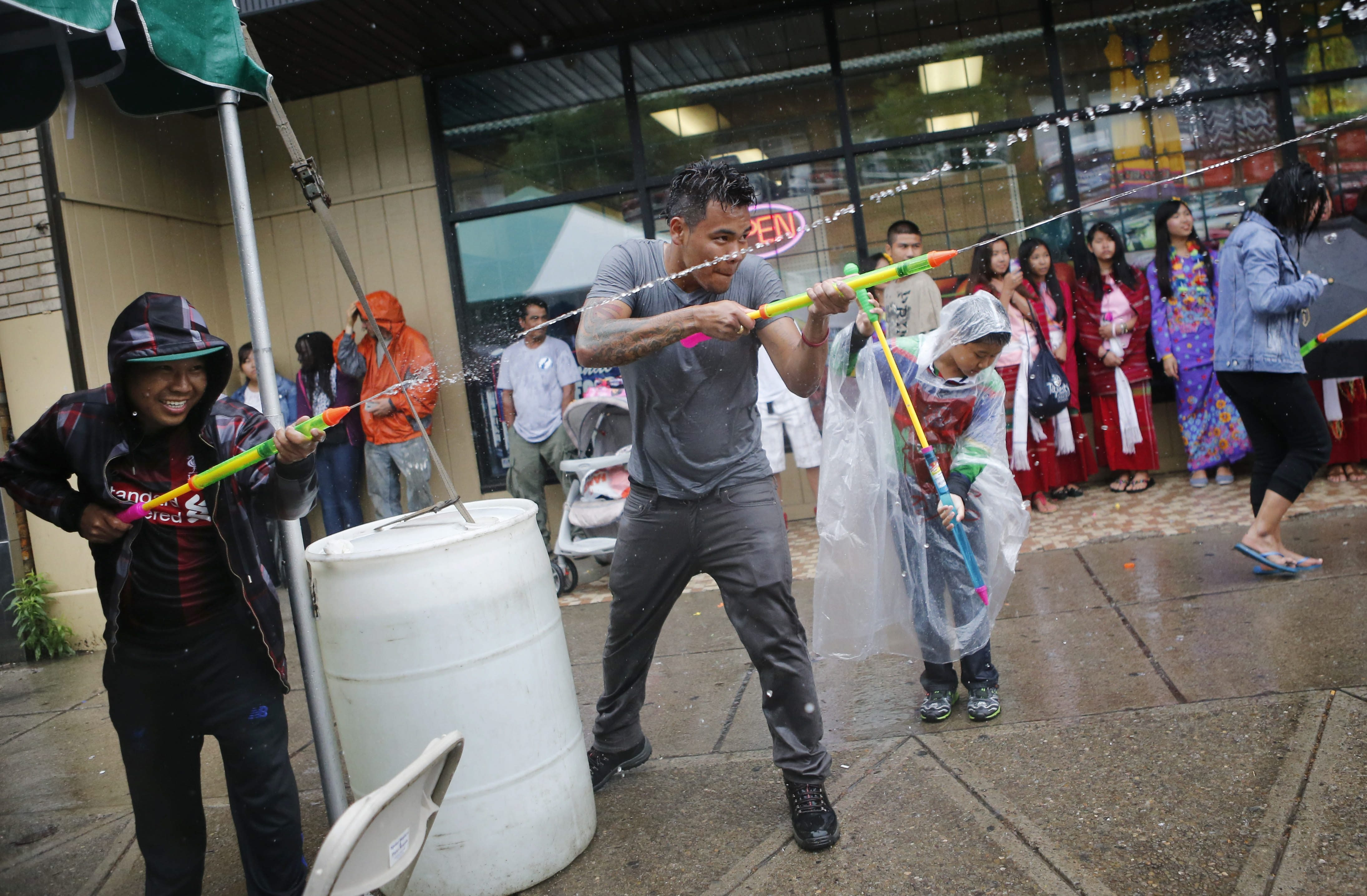Min Saw, left, and Lah A, center, spray revelers with water at the Myanmar Water Festival on Grant Street. Over 200 people gathered to drench each other in a ritual that intends to symbolized purification.