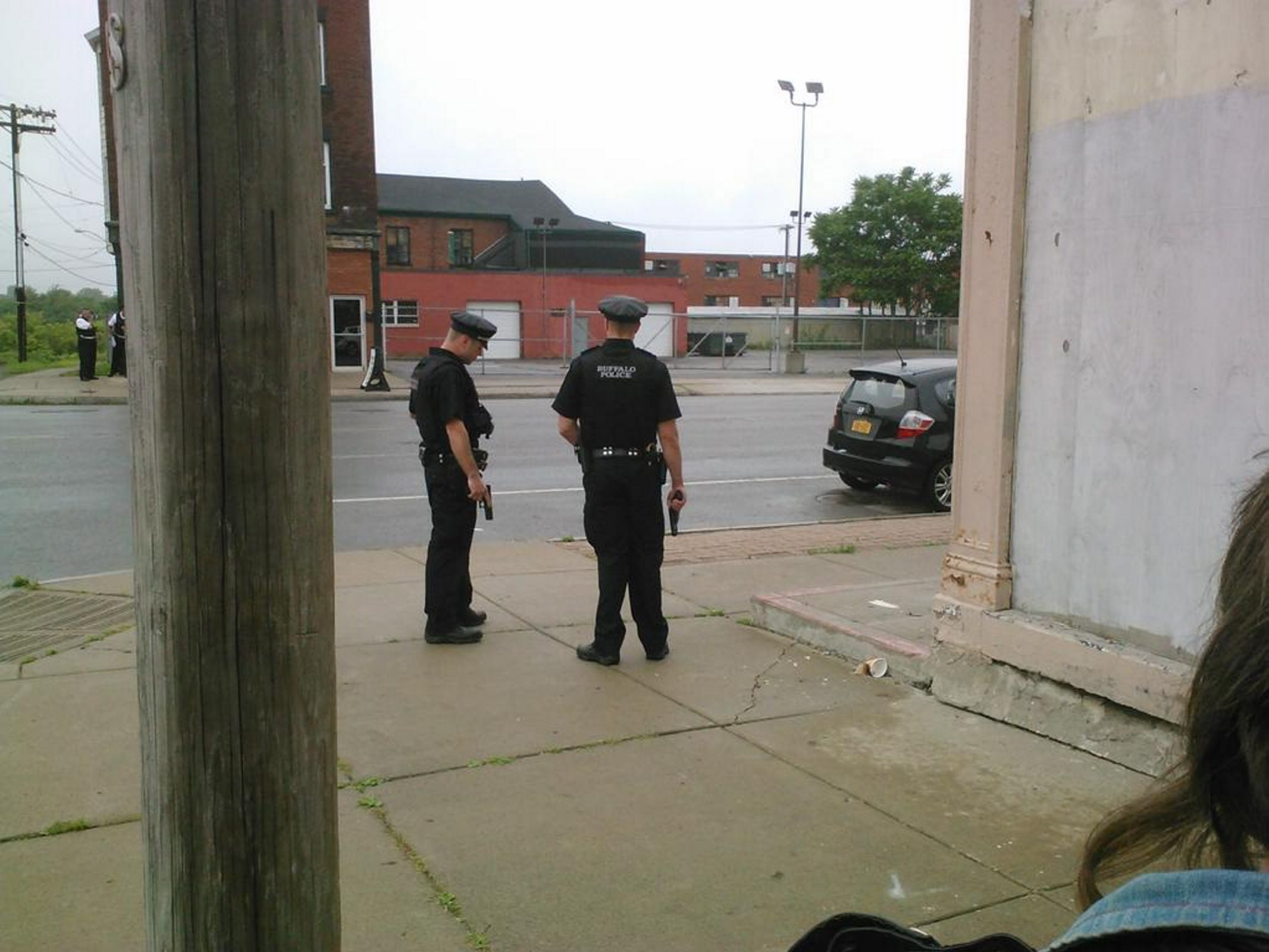 Two Buffalo police officers, with guns drawn, stand guard at an intersection.