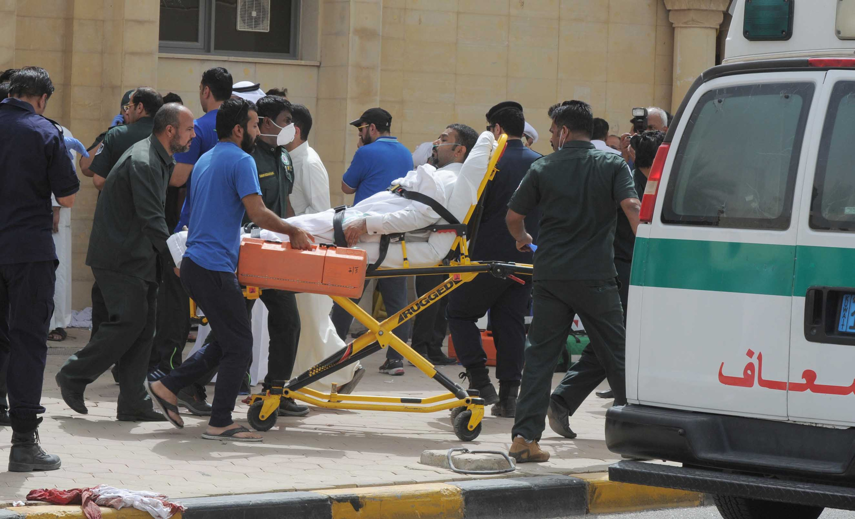 A wounded man is transferred outside the Imam Sadiq Mosque following a suicide bomb blast on June 26, 2015 in Kuwait City, the capital of Kuwait. (TNS)