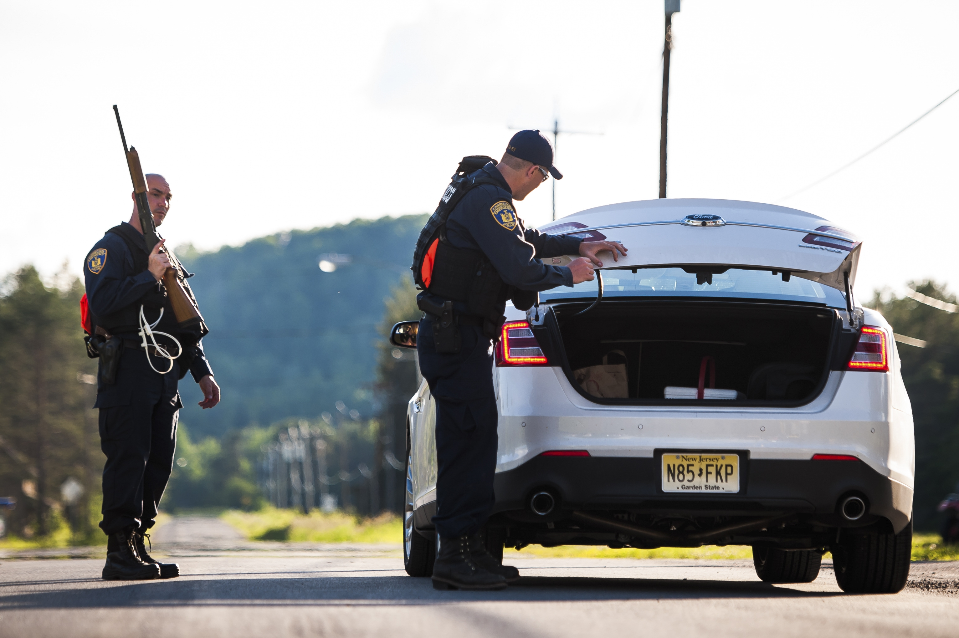 Corrections officers check the trunk of a car near Owls Head, N.Y., June 22, 2015. Forensic evidence indicated that the two killers had been in nearby Mountain View, N.Y., 15 miles west of the Clinton Correctional Facility, within the last 48 hours. (Jacob Hannah/The New York Times)