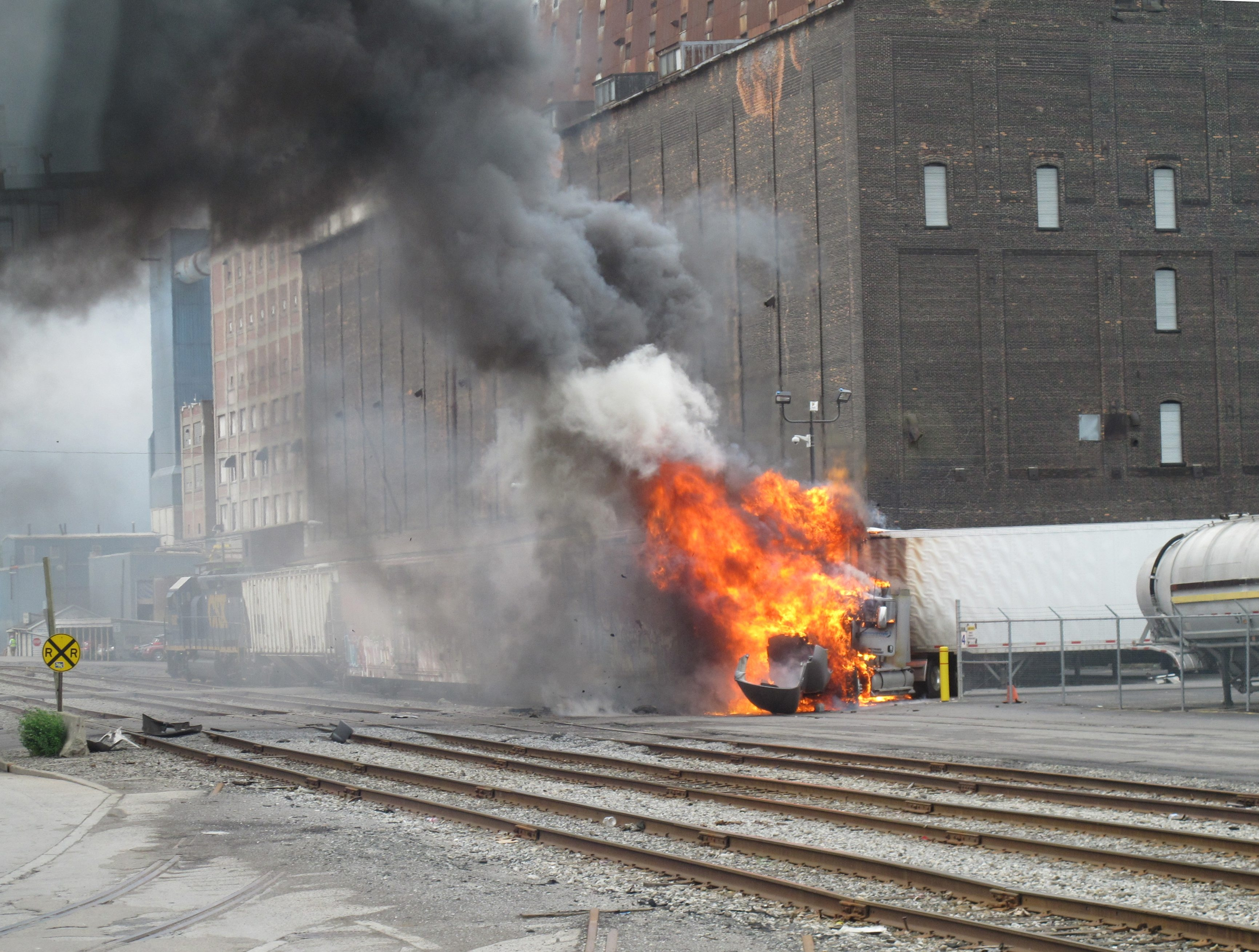 Flames engulf the cab of a tractor-trailer after it was hit by a CSX train on Ganson Street in Buffalo on Tuesday morning.