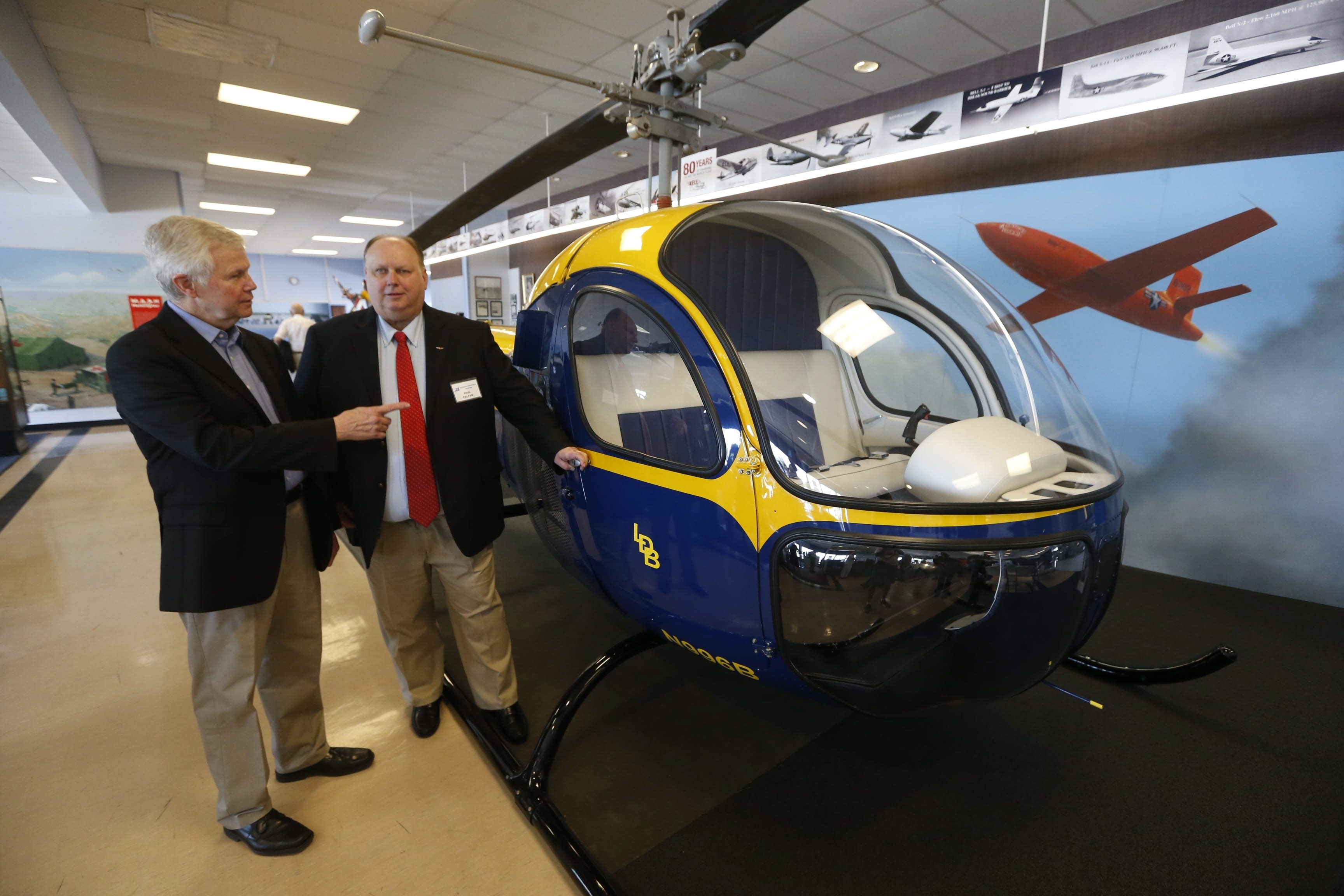 Todd Carlson, left, son of pioneering test pilot Floyd Carlson, discusses Bell helicopter with Paul Faltyn, director of Niagara Aerospace Museum at a display at Buffalo Niagara International Airport. Floyd Carlson helped make aviation history at Union and Losson roads.