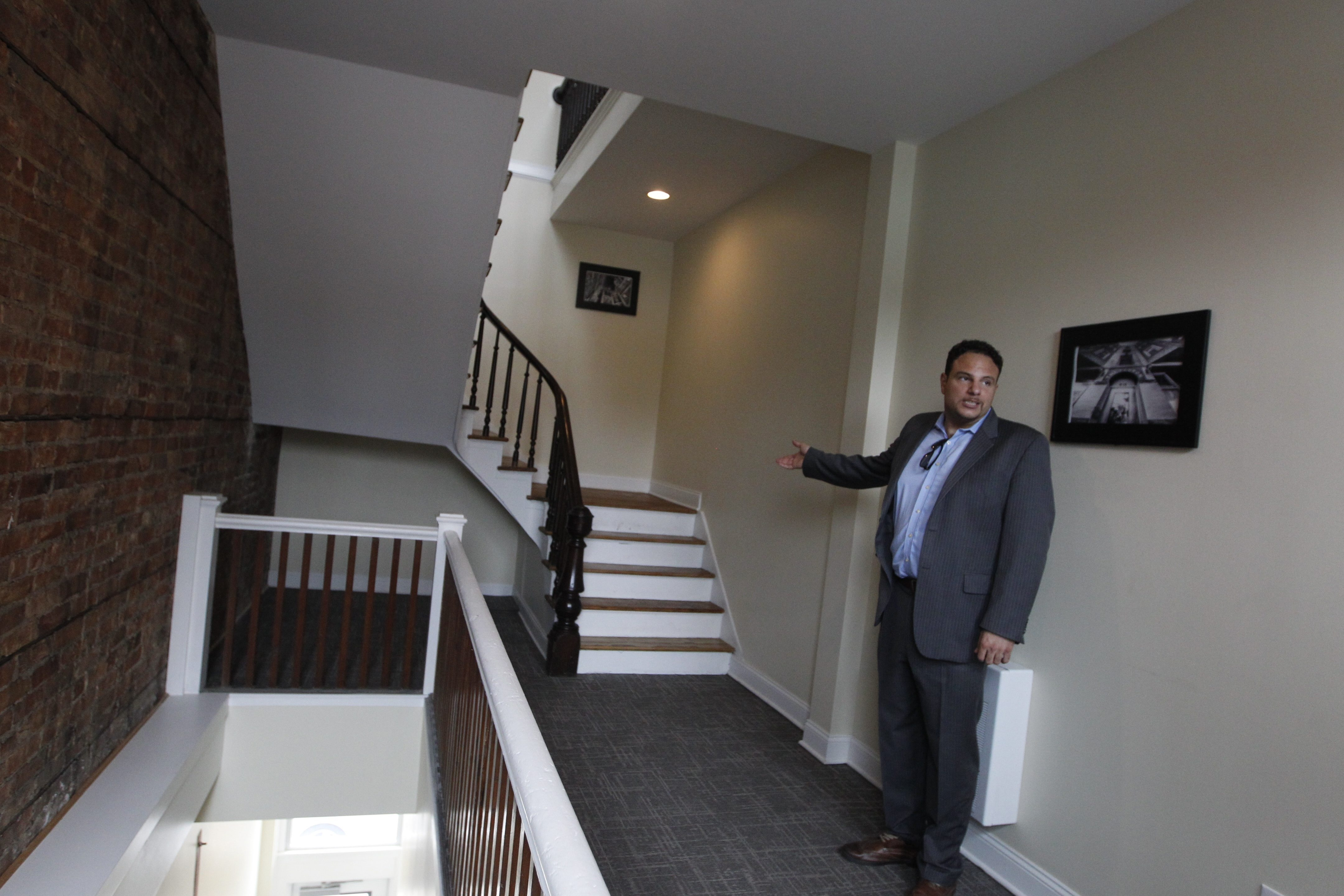Developer Nick Sinatra gives a showing off a staircase on a tour of Fenton Village, the apartments at the corner of Main and Ferry in Buffalo, N.Y., on Tuesday, June 23, 2015. (John Hickey/Buffalo News)