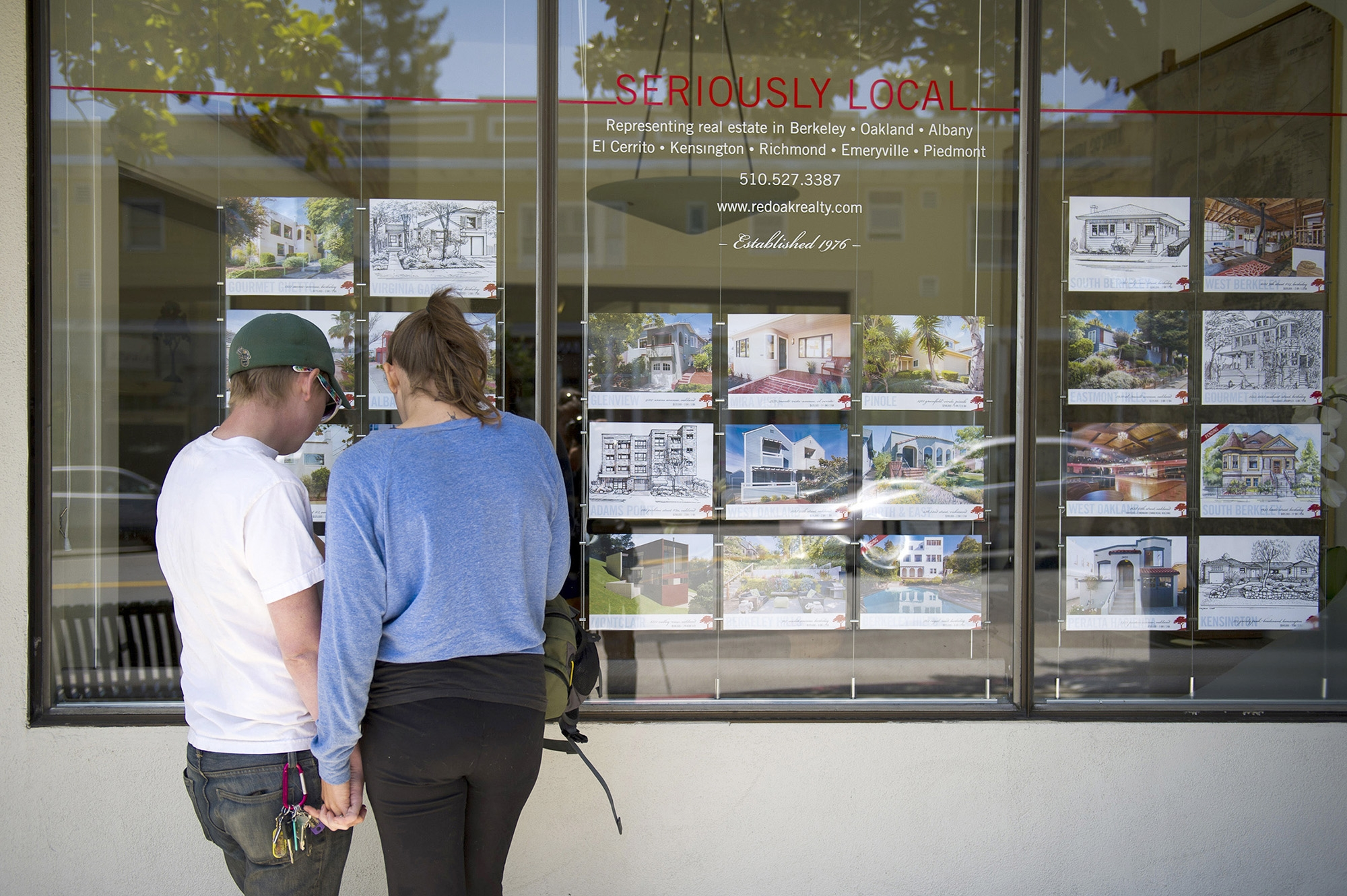 Pedestrians stop to look at fliers listing homes for sale at a Red Oak Realty office in Berkeley, Calif.