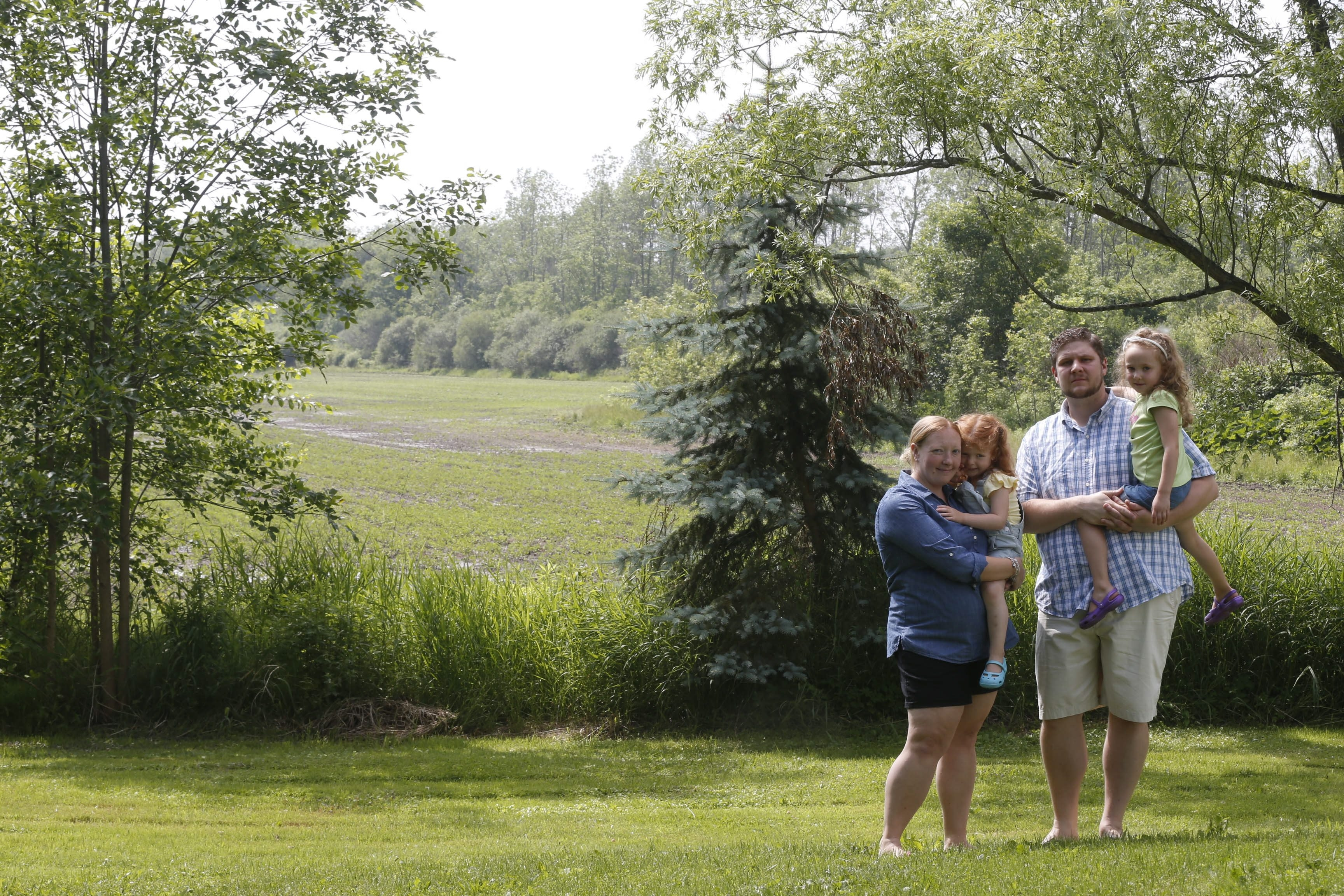 Kelly and Mike Monde with children, Emily, 3, left, and Julia, 4, in the backyard of the Beach Ridge Road home they purchased last summer. The Mondes are alarmed by a plan to build a natural gas compressor behind the house.