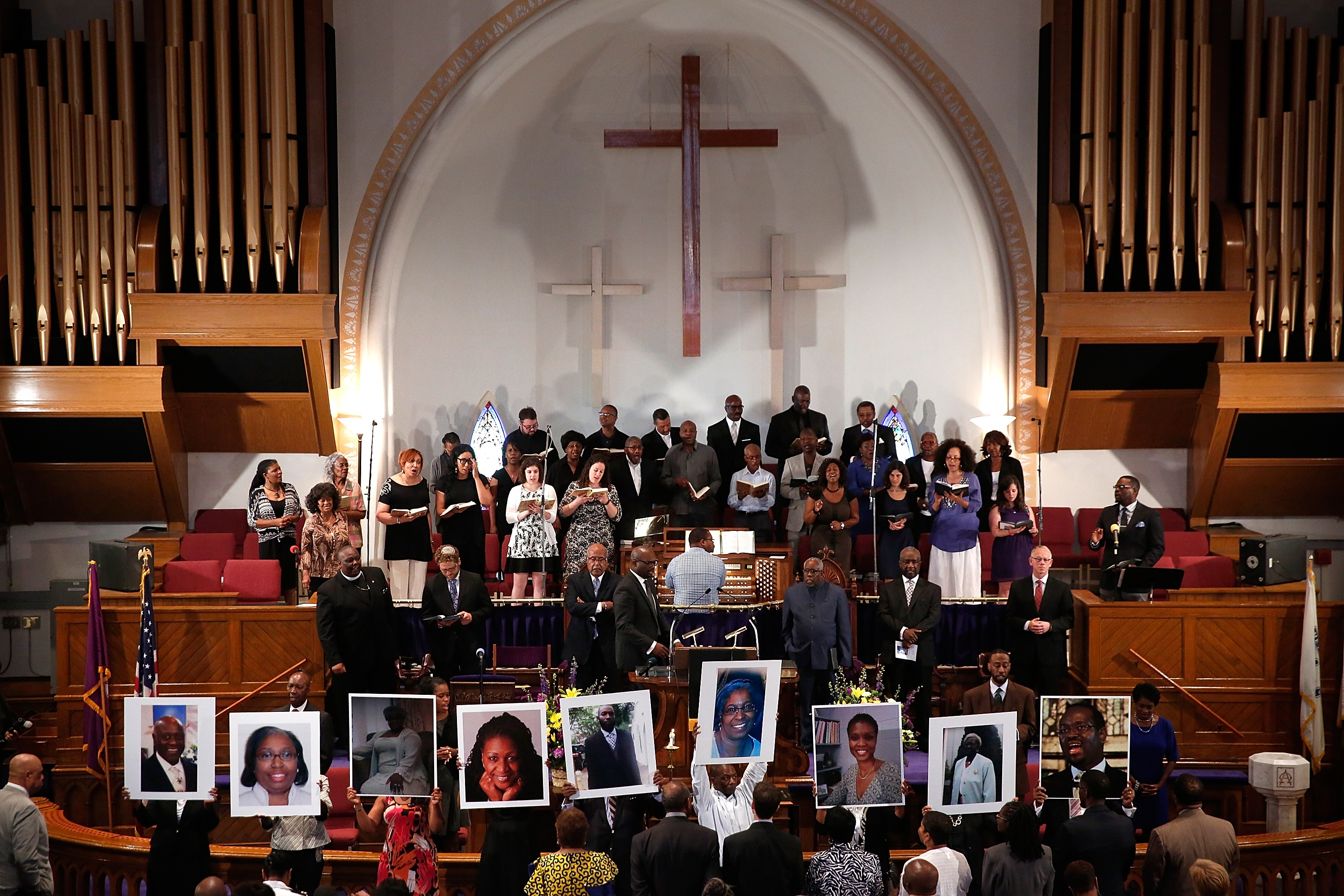 Congregants hold up photos of the victims of the church shooting in Charleston during a prayer vigil at the Friday at the the Metropolitan AME Church in Washington, D.C. (Getty Images)