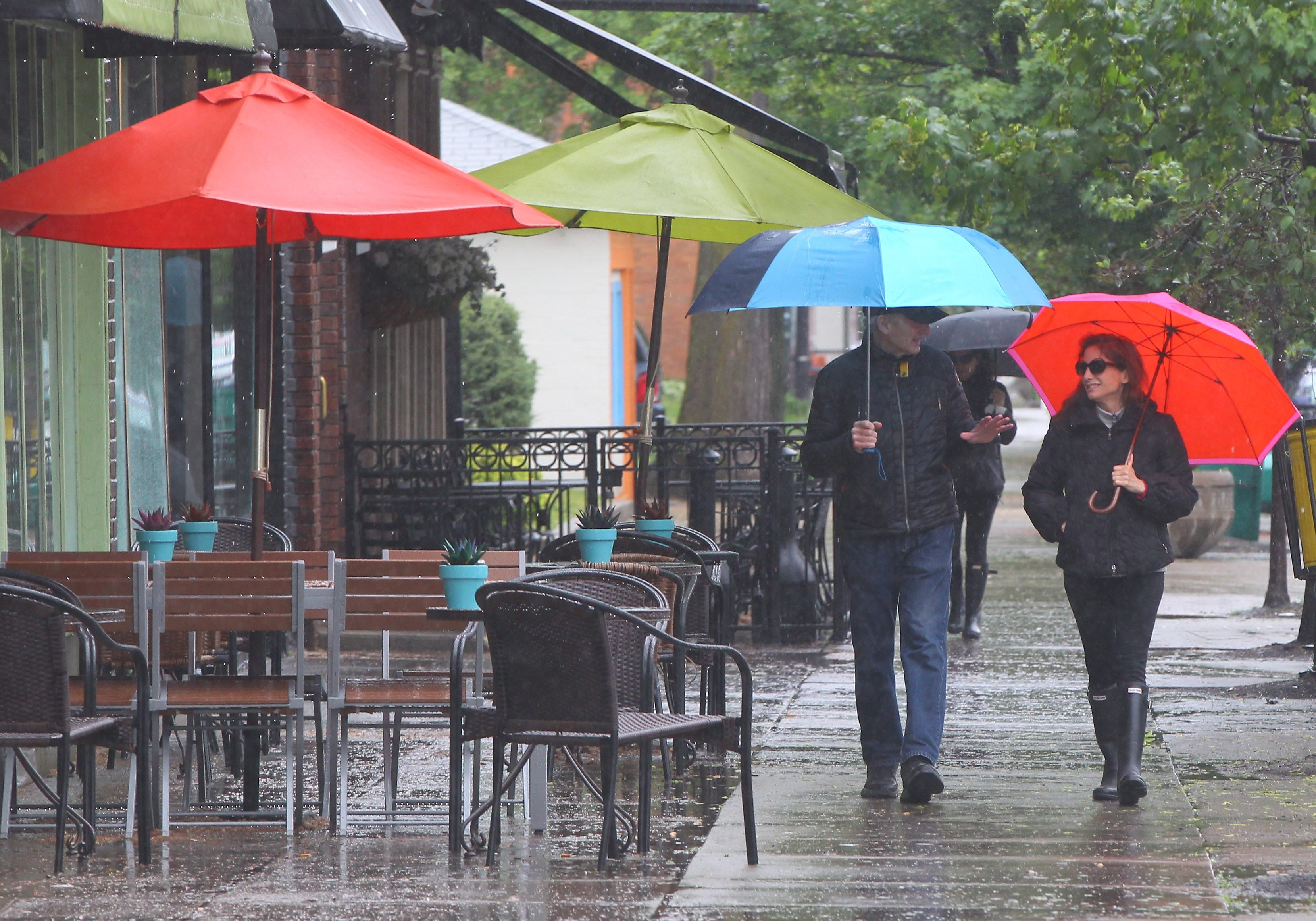 Ted and Lisa Bickford walk through the wind and rain with colorful umbrellas on Elmwood Avenue on May 31, 2015.