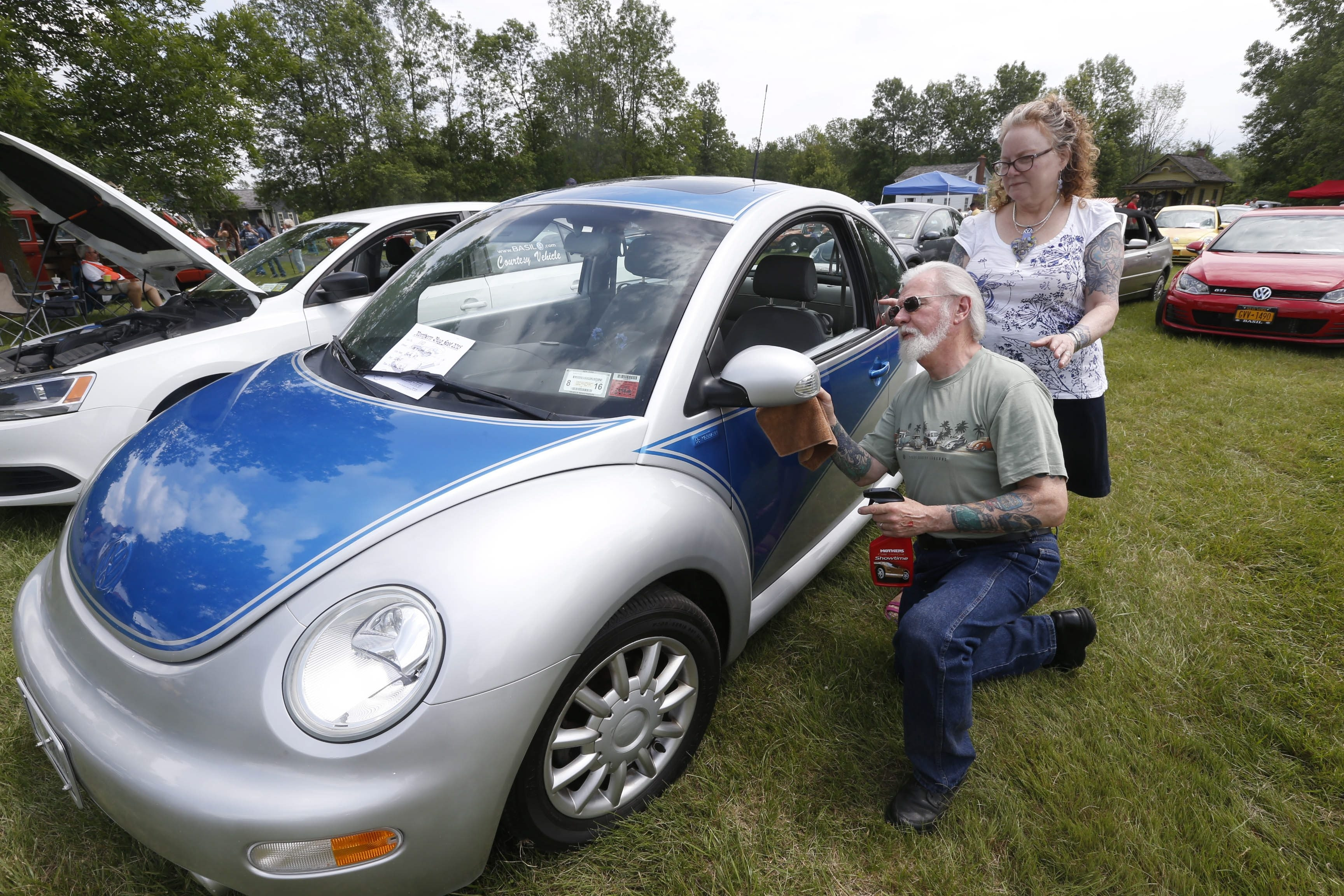 "Ken and Leah Corey of Bath polish their custom-painted 2005 Volkswagen Beetle at Bugfest. Though Ken said that he does not usually name the 23 bugs he's owned throughout his life, he named the silver and blue metallic car – the ""youngest"" car in his collection – Belle, from ""Beauty and the Beast."""