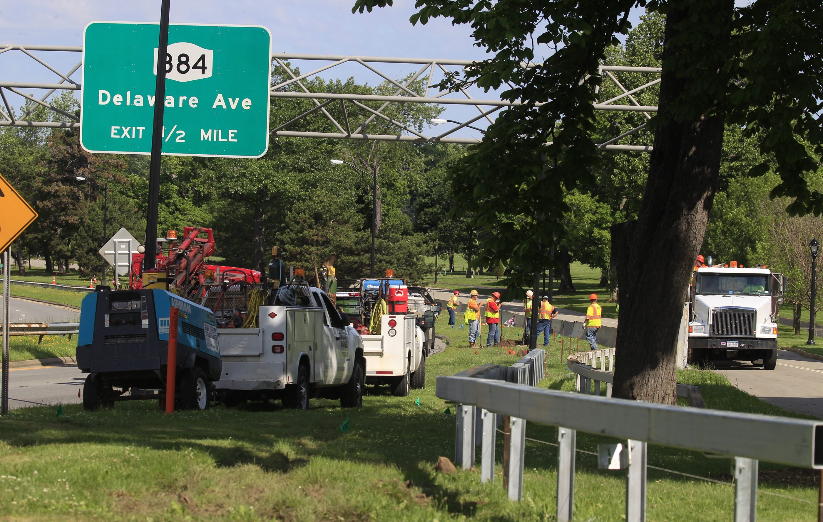 Workers install guardrails at Route 198 and Ring Road at Delaware Park in Buffalo on June 15. (John Hickey/Buffalo News)