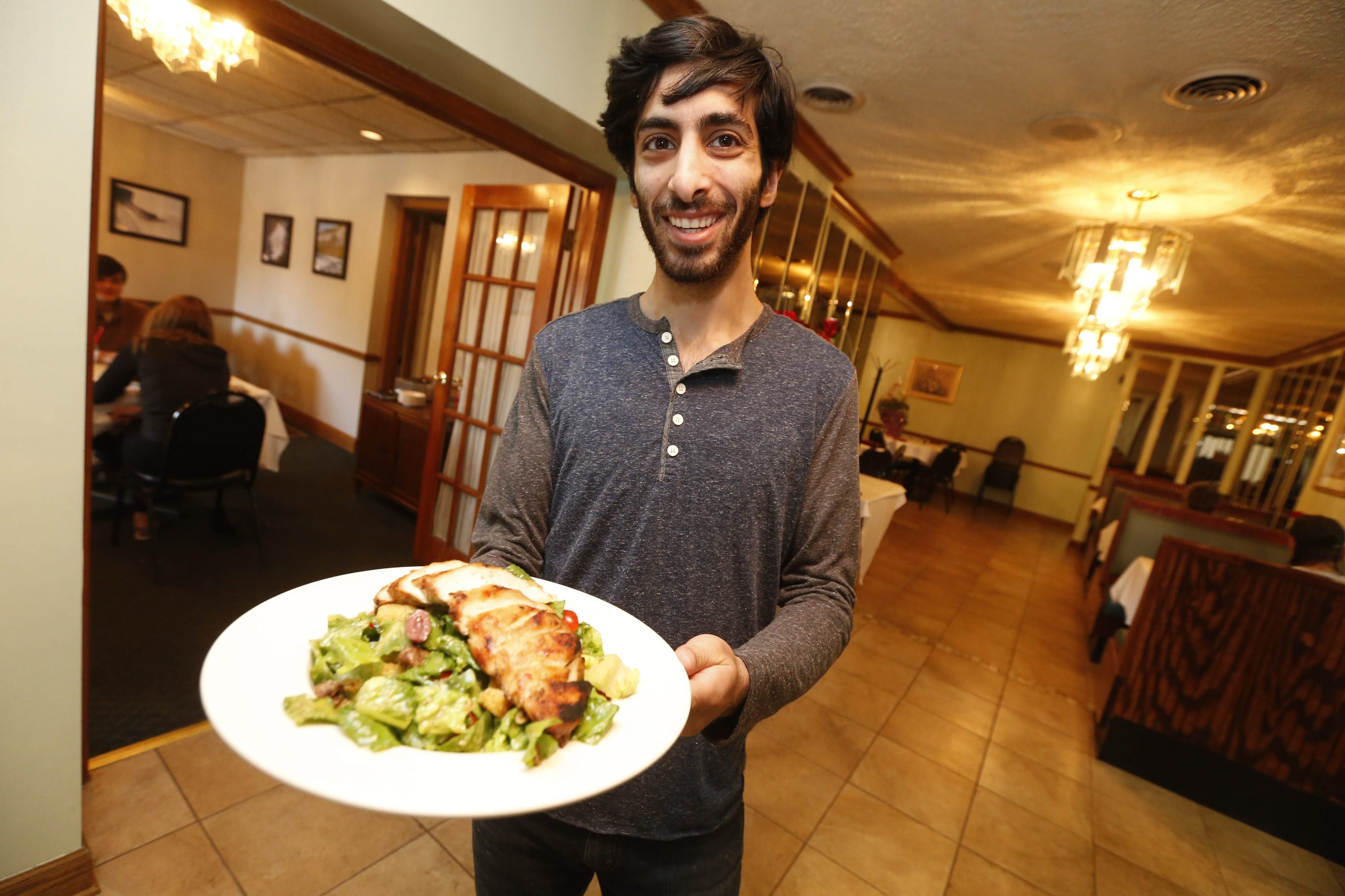 Robert Kirkham/Buffalo News JJ Merhi, whose family owns 755 Restaurant and Lounge in Niagara Falls, shows off the popular Caesar Salad with Chicken. The restaurant specializes in American, Italian and Lebanese foods.
