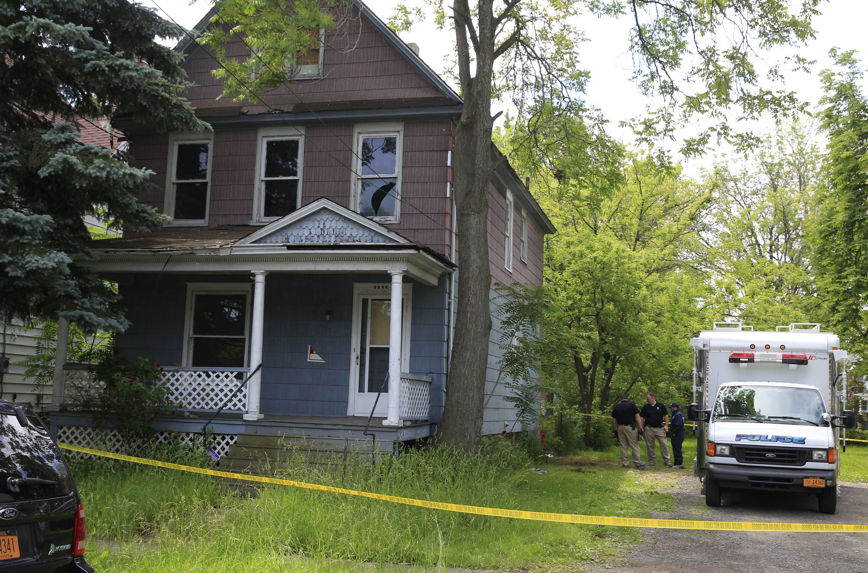 Police crime scene investigators talk at abandoned home at 1129 Willow Ave. in Niagara Falls, where body was found.