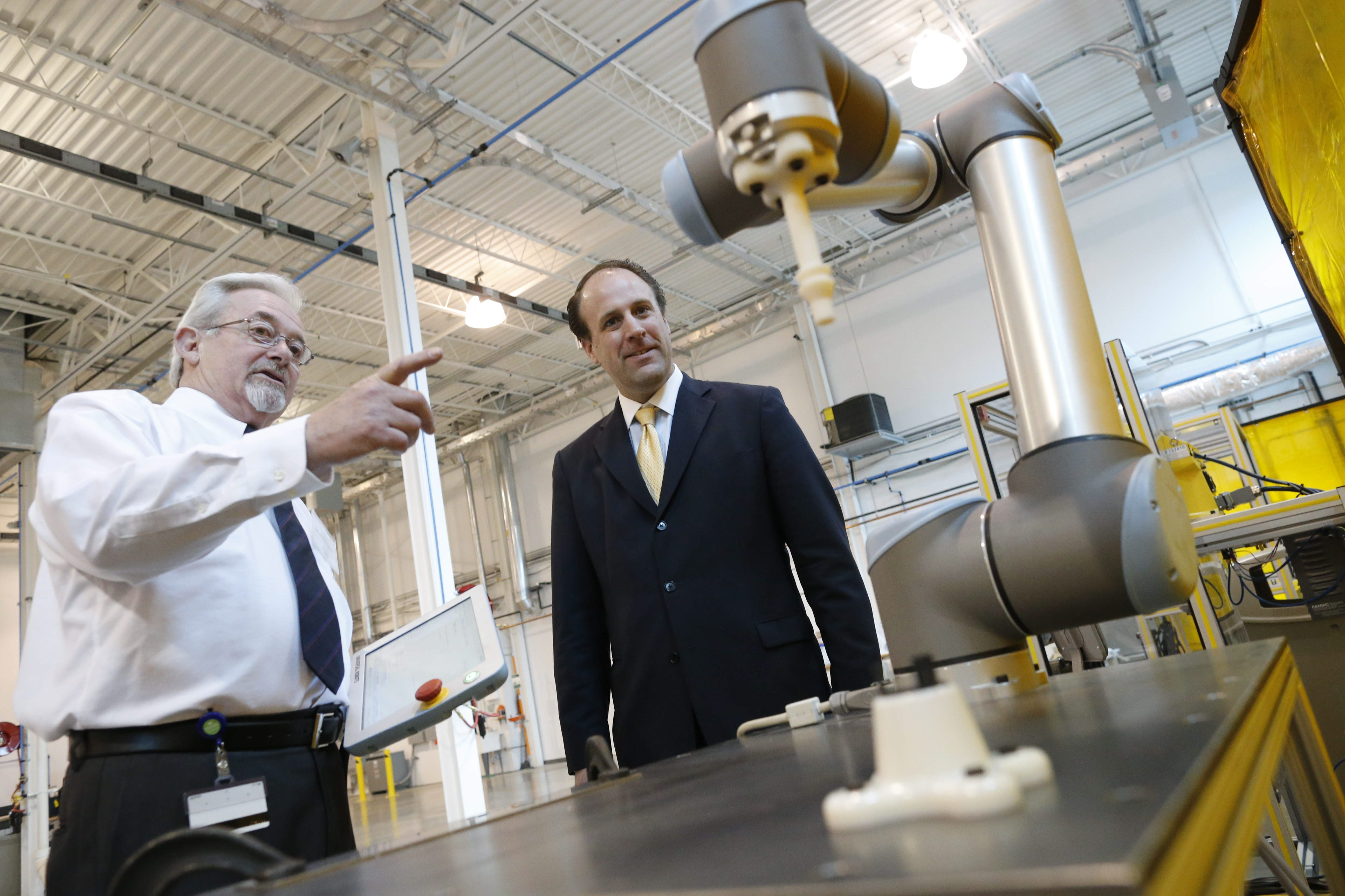 "Ron Brown, technology leader at EWI, left, and Gardner Carrick, vice president of strategic initiatives at the Manufacturing Institute, examine a new ""cobot"" during a tour of Buffalo Manufacturing Works on Friday."