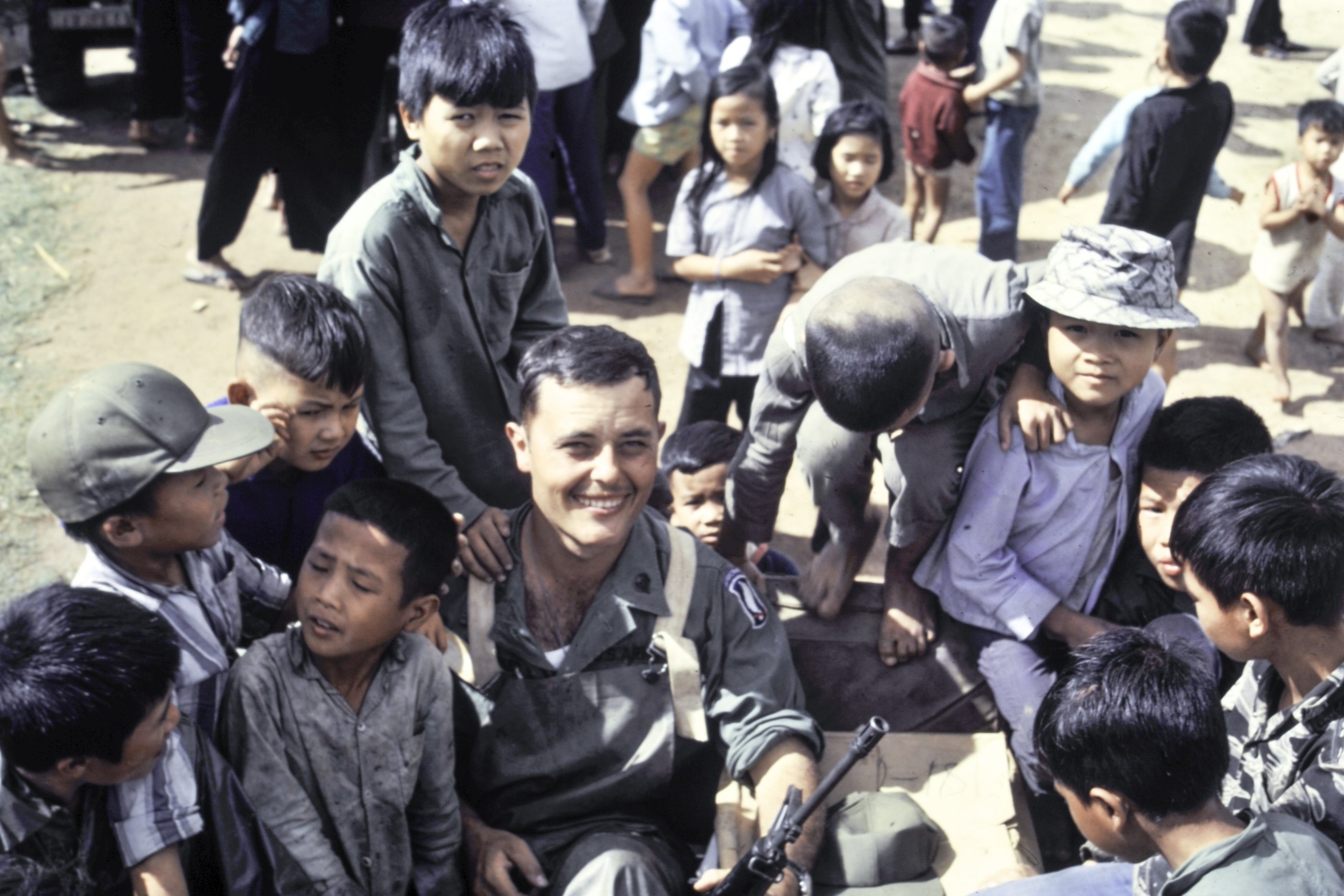 Army Spc. 4th Class Richard Szczepaniec while helping young Vietnamese villagers in wartime as part of Medical Civic Action Program, or MEDCAP.