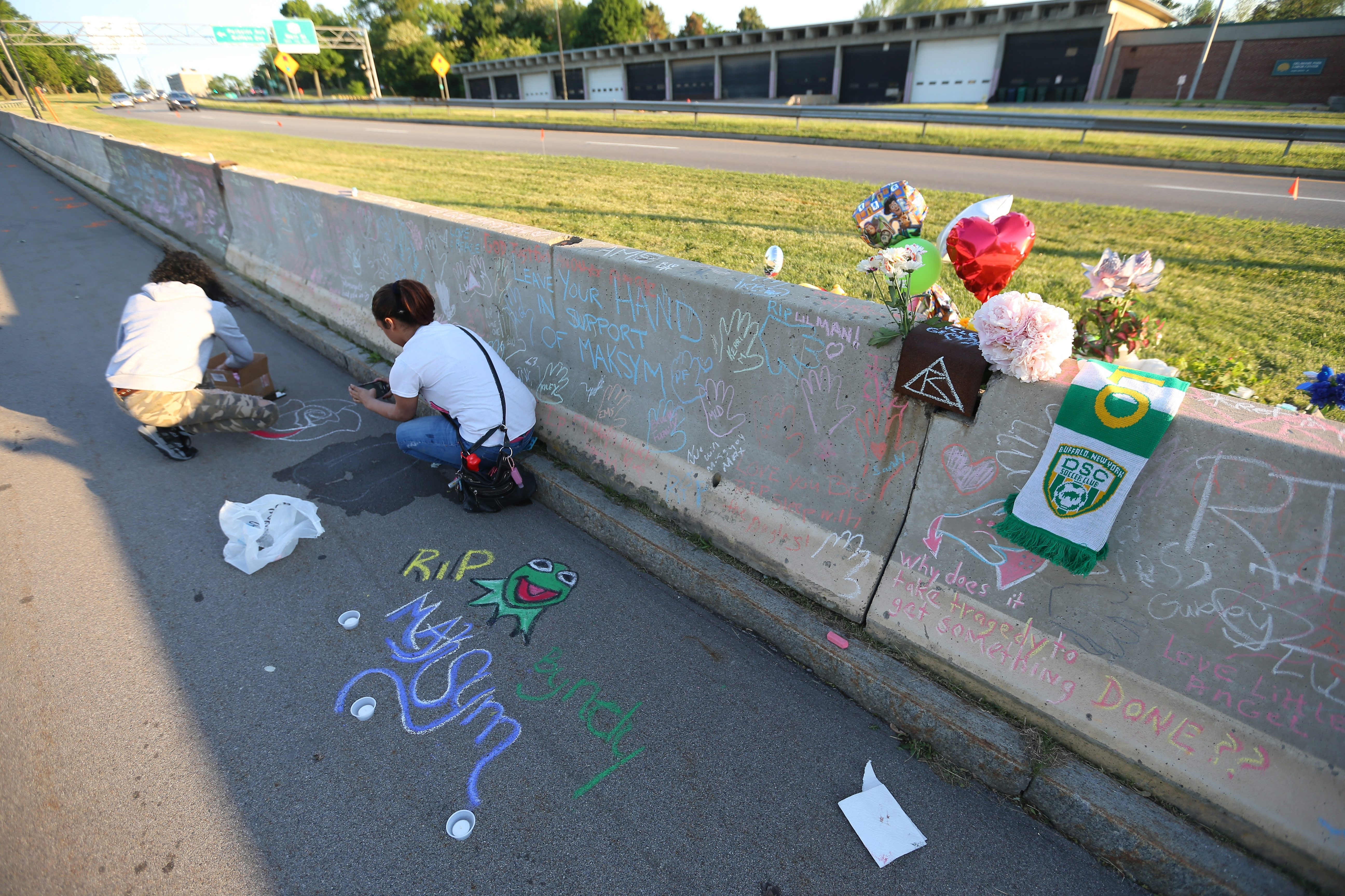 People write with chalk in Delaware Park after a vigil in support of the Sugorovskiy family. Maksym Sugorovkiy was struck and killed on the park's Ring Road when a car left the Scajaquada Expressway and crossed the median.   (Mark Mulville/Buffalo News)