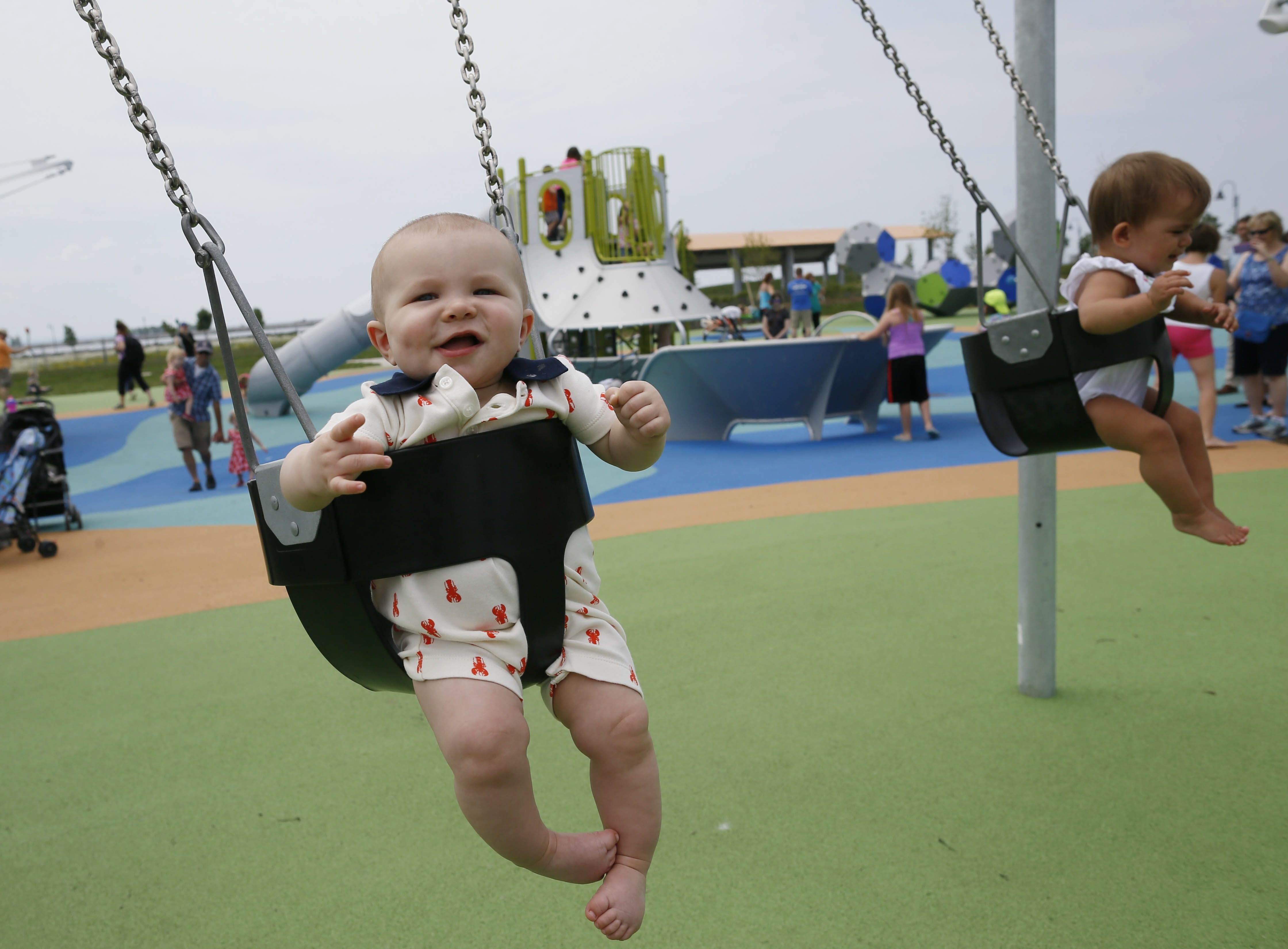 Seven-month-old Preston Rachow gets in the swing of things Tuesday at the new playground at Buffalo Harbor State Park.