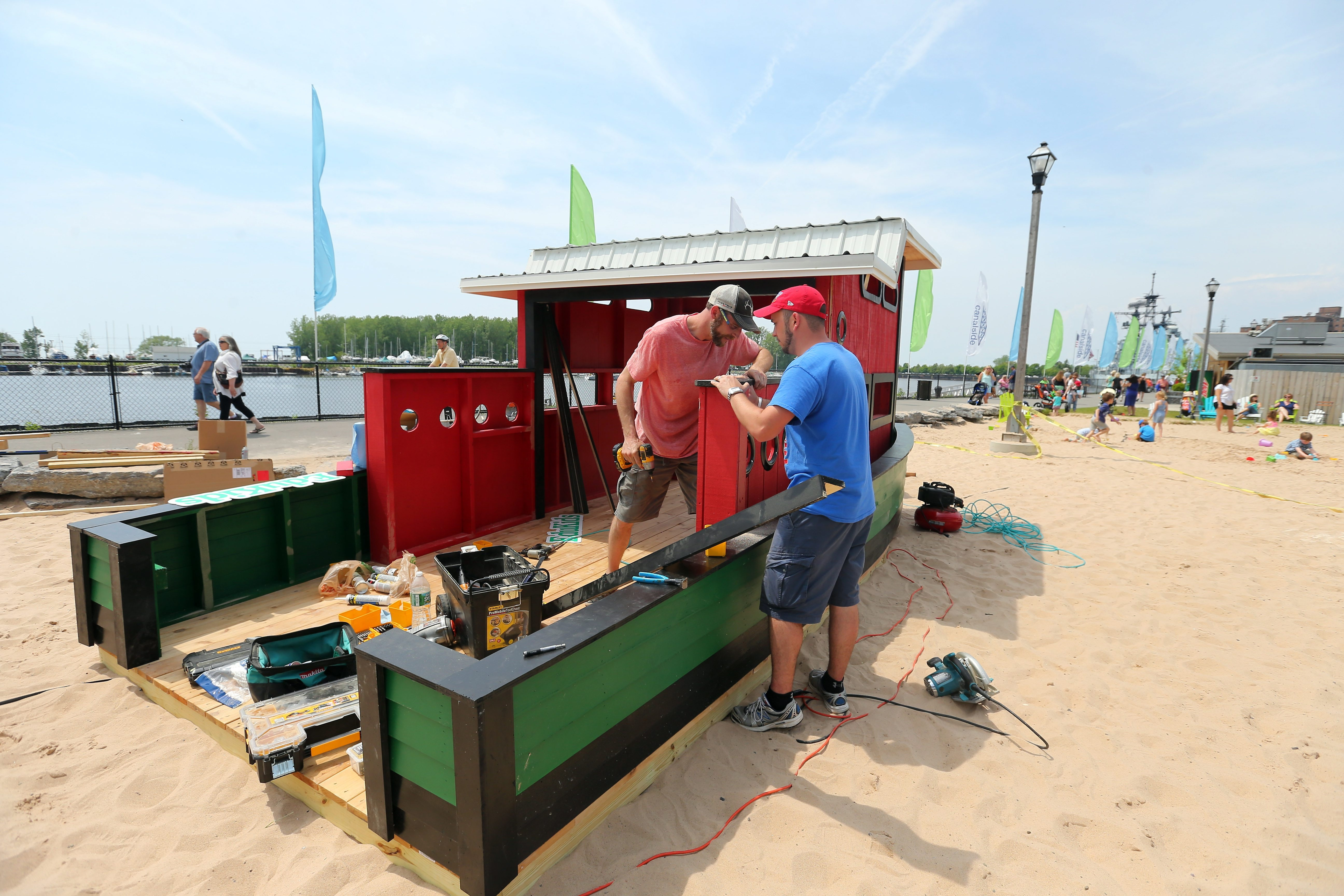 John Clavette, left, and Aaron Quinn, right, build a tugboat play structure at the children's beach at Canalside in Buffalo on June 5.