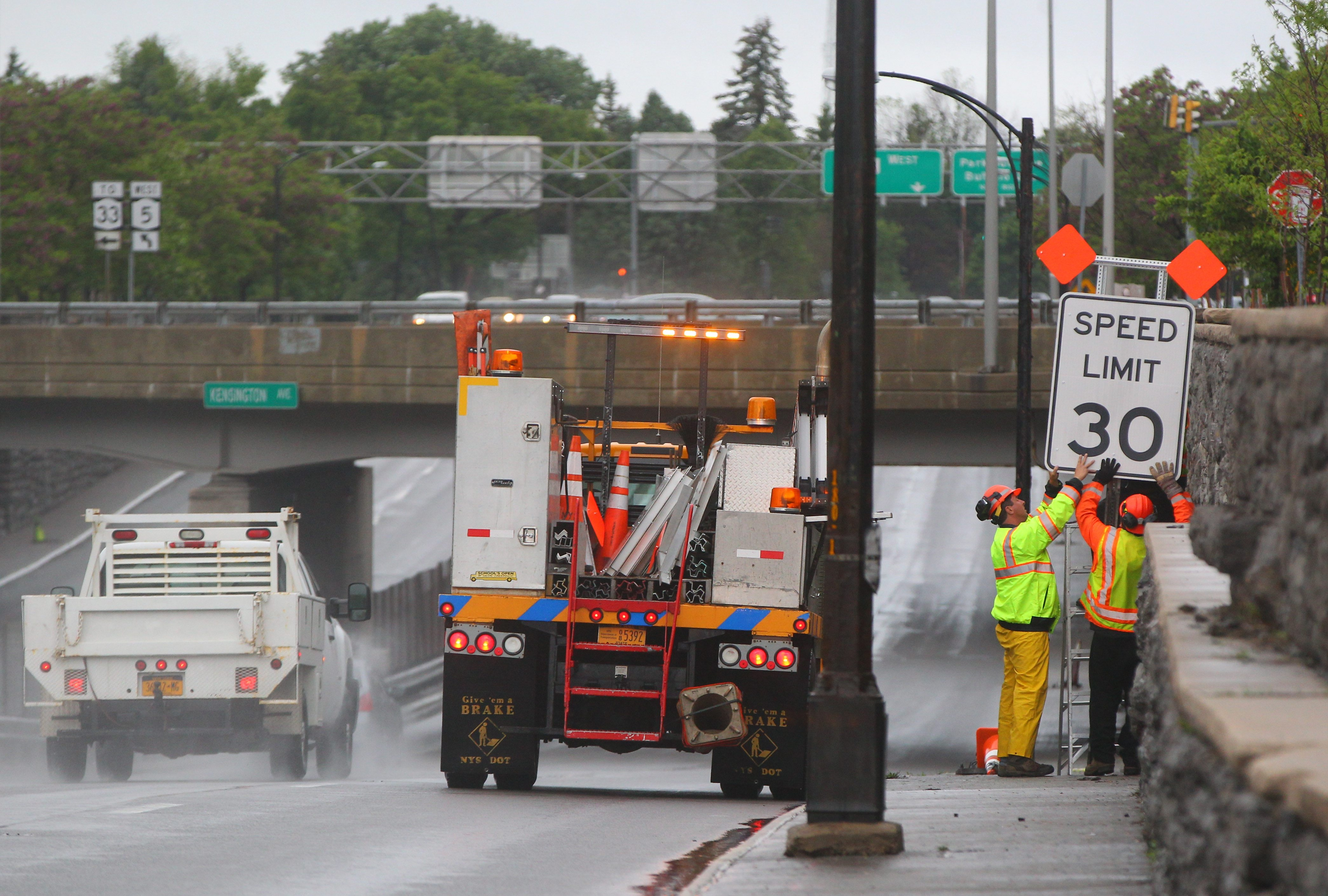 State Department of Transportation crews replace the speed limit sign on the Scajaquada Expressway (Route 198) near Main Street in Buffalo on Sunday, May 31, 2015.