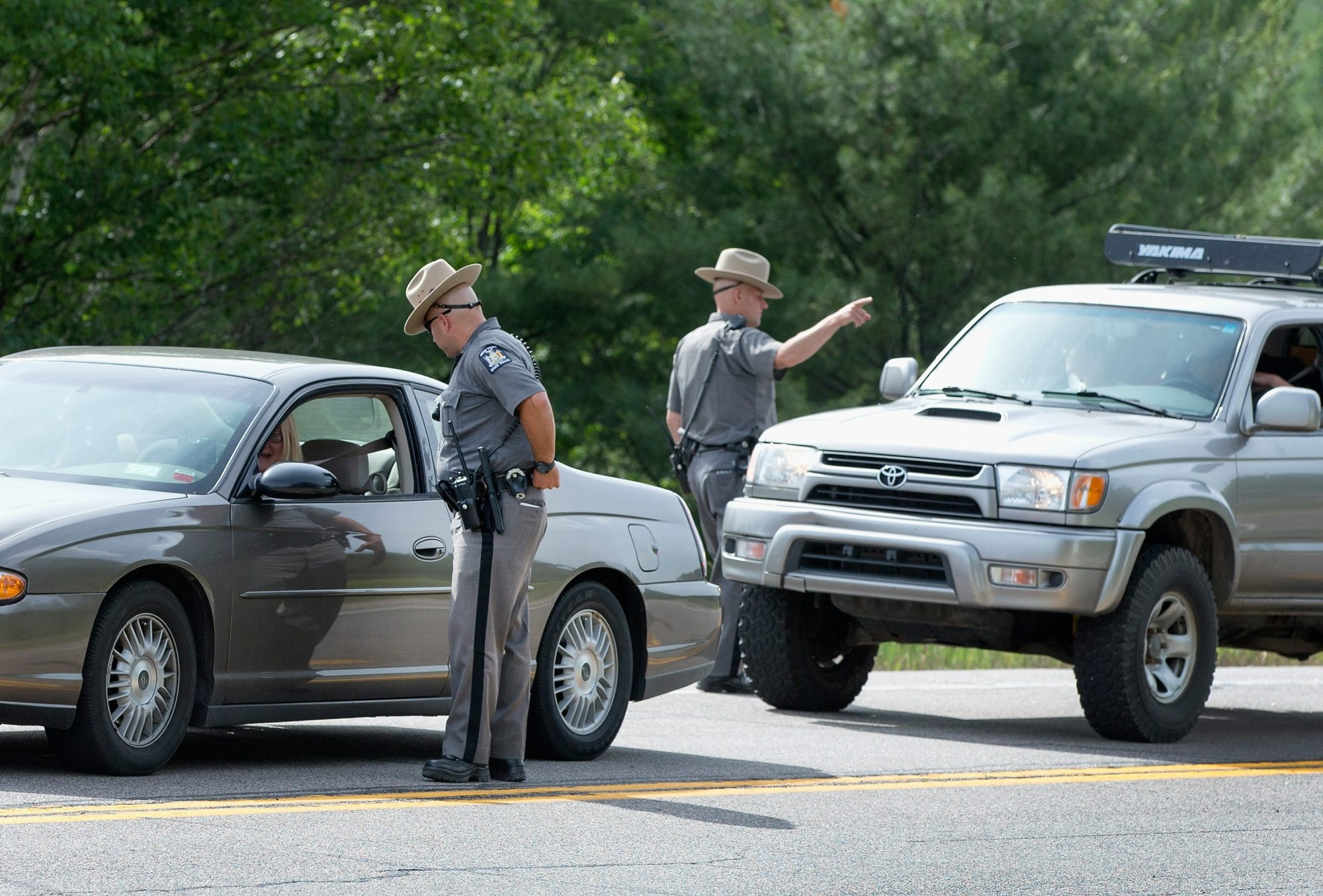 New York State Police officers man a roadblock along Highway 30 as the manhunt for escaped convict David Sweat continues Saturday near Malone.