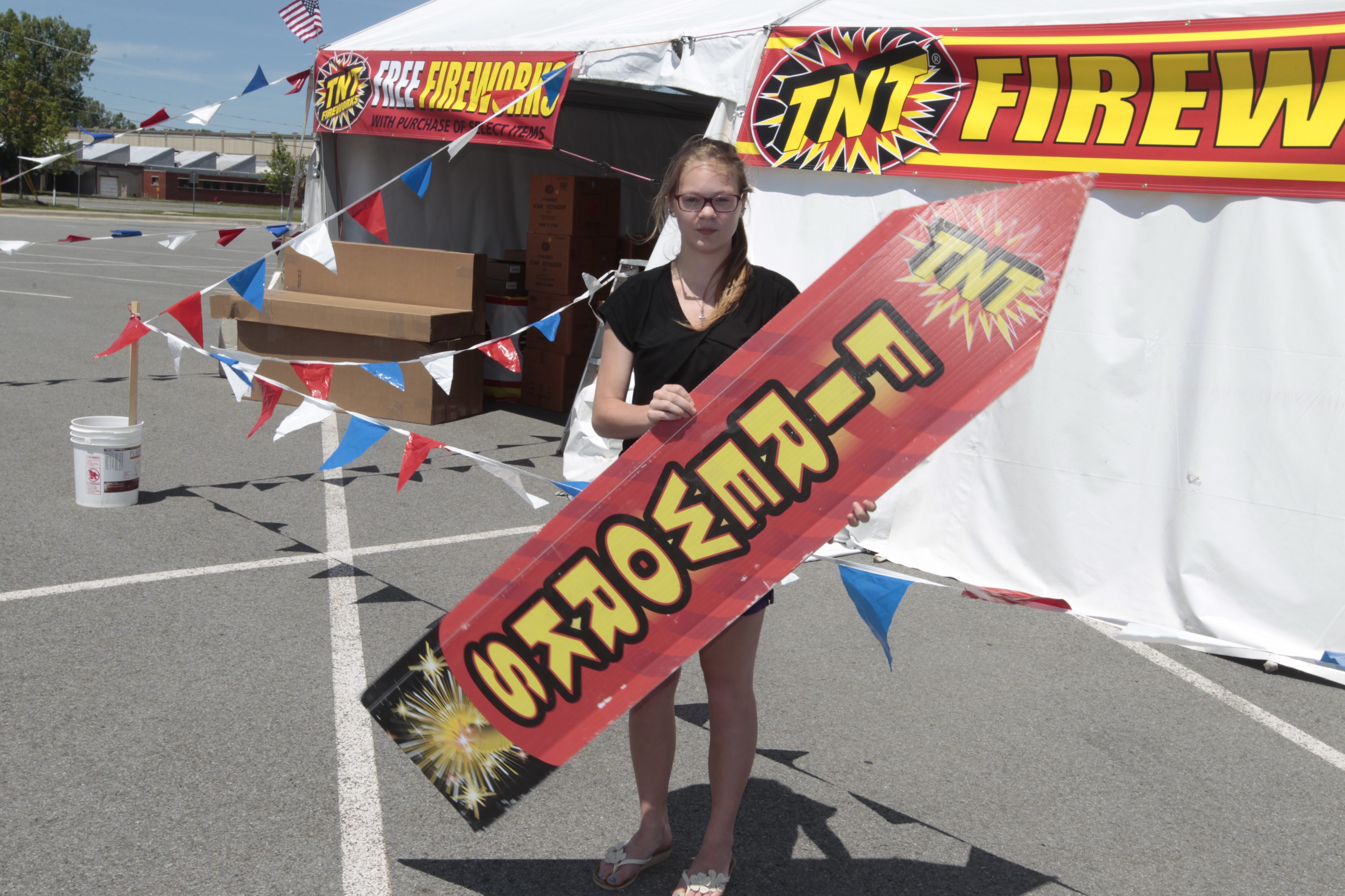 JoAnna Handler moves a sign as she helps set up a tent to sell sparklers and fireworks in the Walmart parking lot in North Tonawanda.