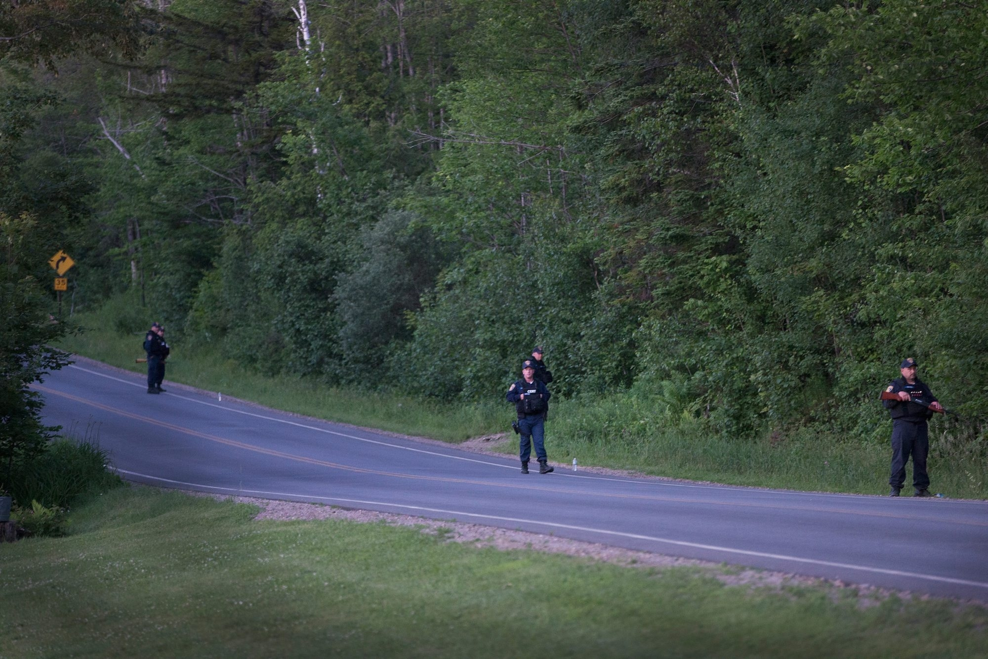 Department of Correction officers stand guard along a wood line near the scene where escaped convict Richard Matt was shot and killed by law enforcement officers on June 26 in Malone.
