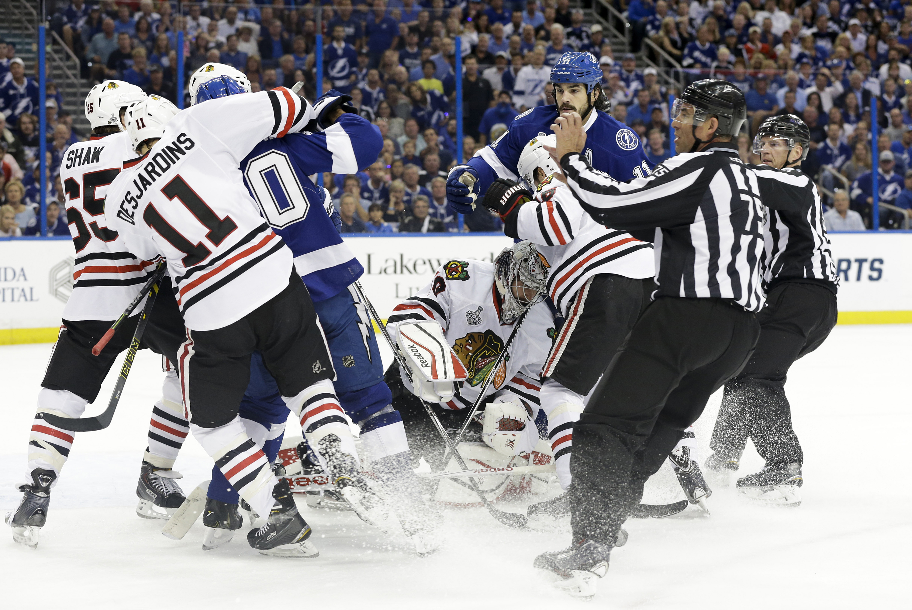 Referees beak up a scrum between the Lightning and Blackhawks during the first period of Game One in Tampa Wednesday.