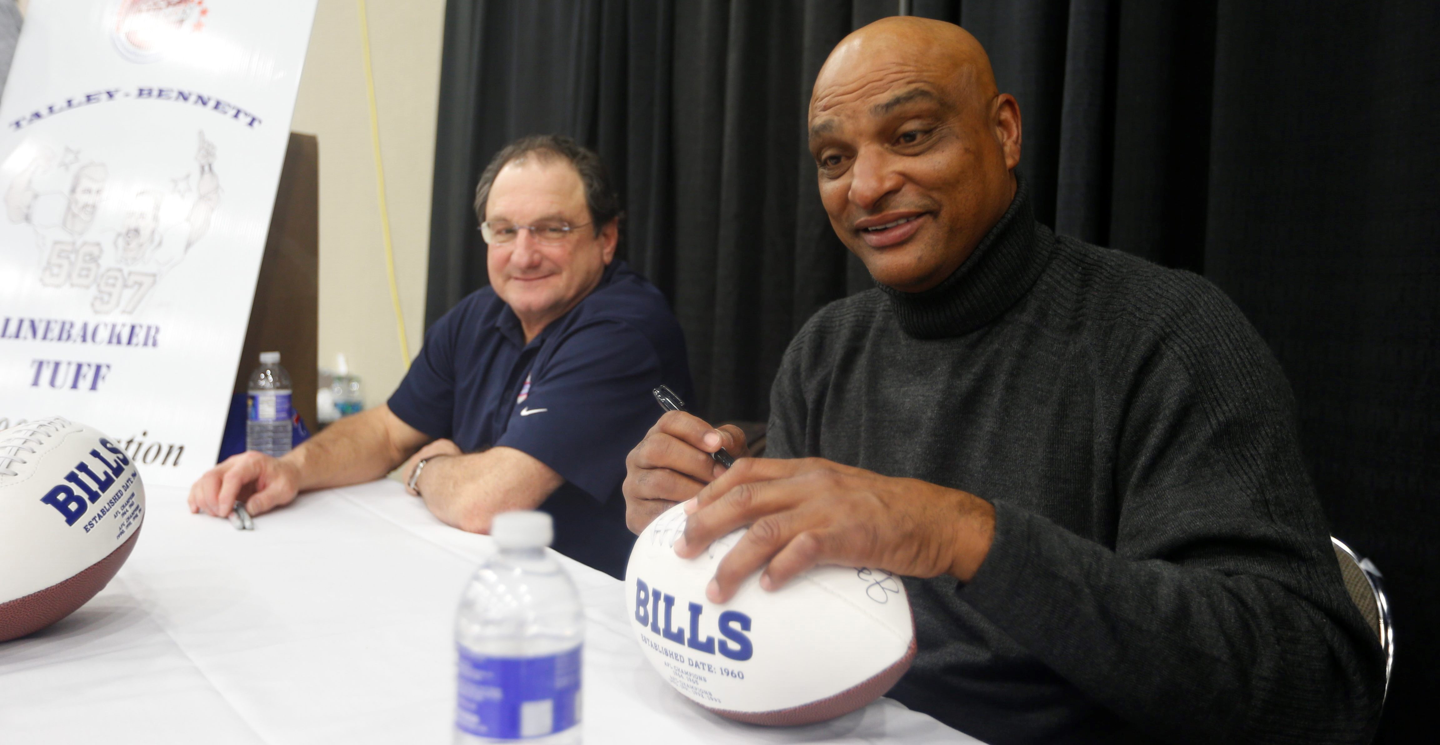 Darryl Talley, right, signs autographs at the Buffalo Auto Show, along with fellow Bill Lou Piccone, in February. (John Hickey/News file photo)