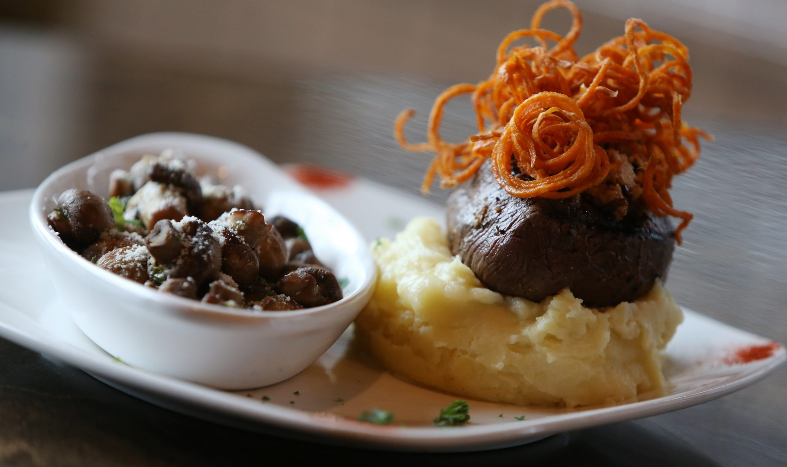 The 8-ounce grilled center-cut filet mignon is topped with maple bourbon-bacon compound butter and a crispy sweet potato nest, presented over Yukon Gold whipped potatoes, saved with a side of garlic, white wine and butter-sautéed baby mushrooms. (Sharon Cantillon/Buffalo News)