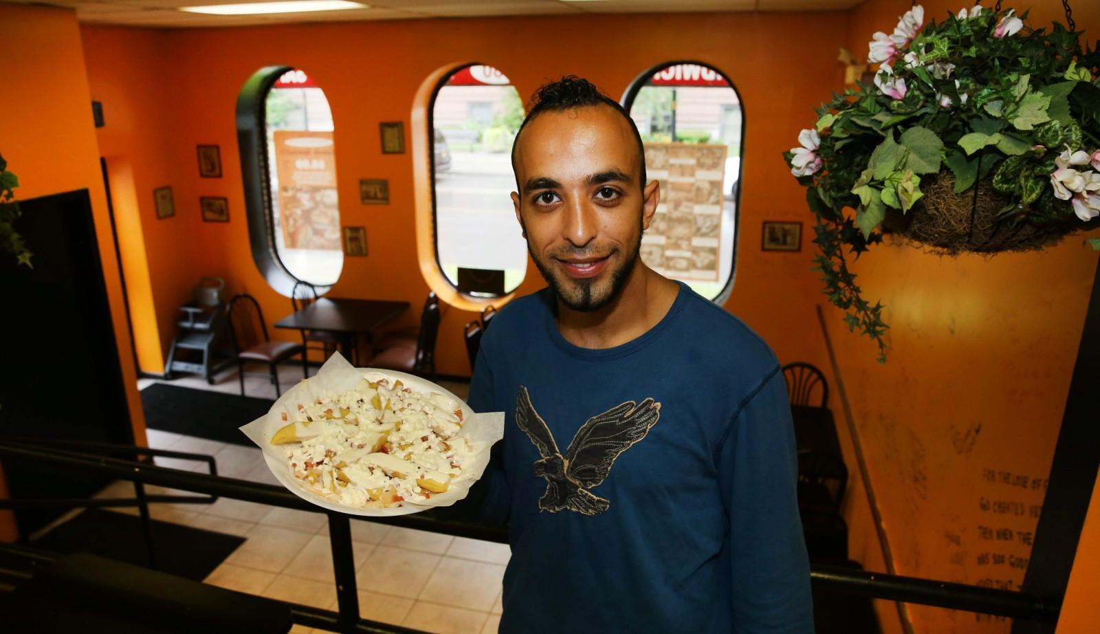 Manager Antewan Fanous presents Venus Mediterranean's popular Greek fries, made with feta cheese, Greek dressing and a housemade garlic sauce. (Sharon Cantillon/Buffalo News)