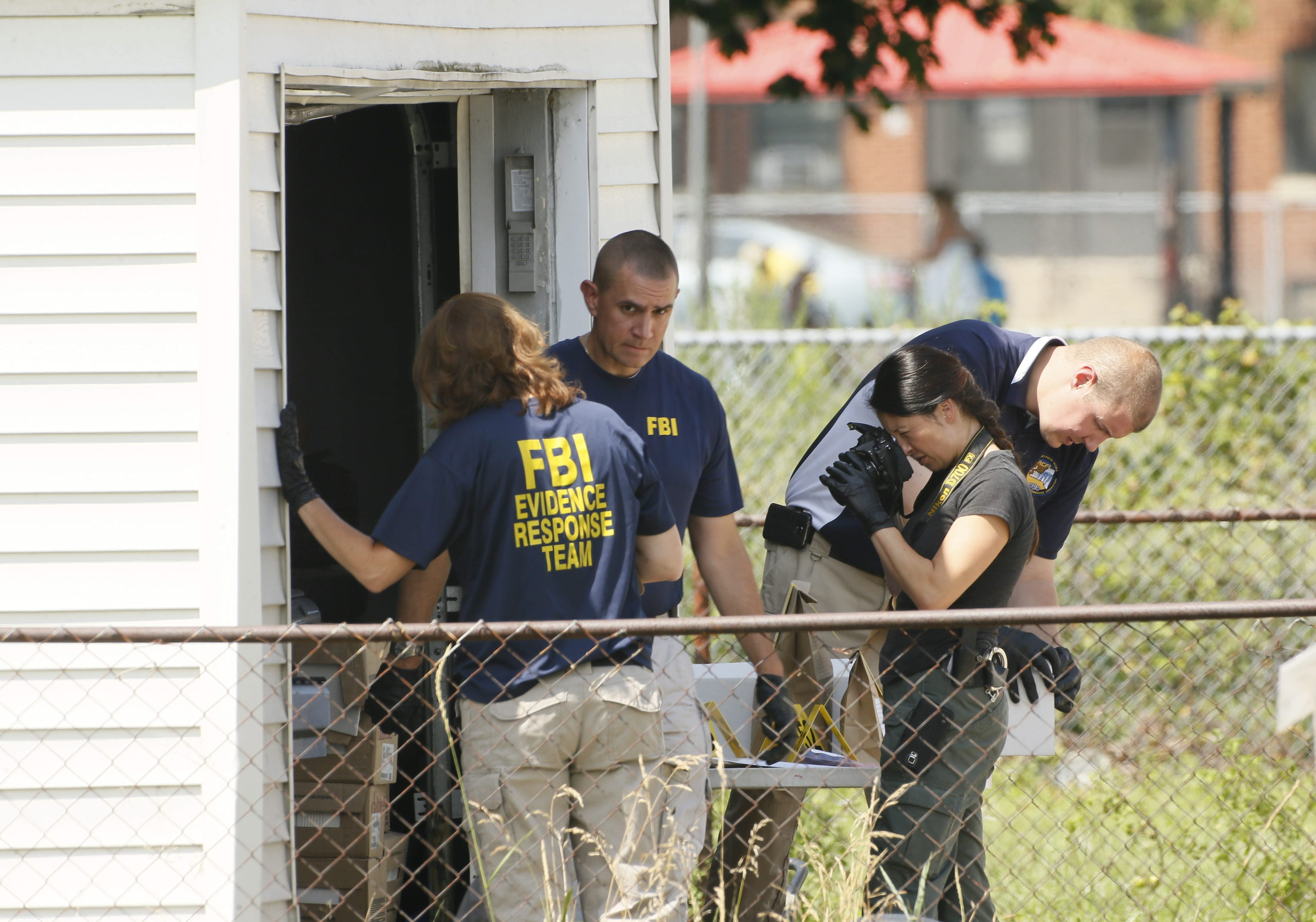 Members of the FBI Evidence Response Team collect materials in the garage of a home on Olcott Street in Lackawanna while executing a search warrant, Wednesday, July 29, 2015.  The U.S. Attorney has announced terrorism related charges against Arafat M. Magi.  (Derek Gee/Buffalo News)