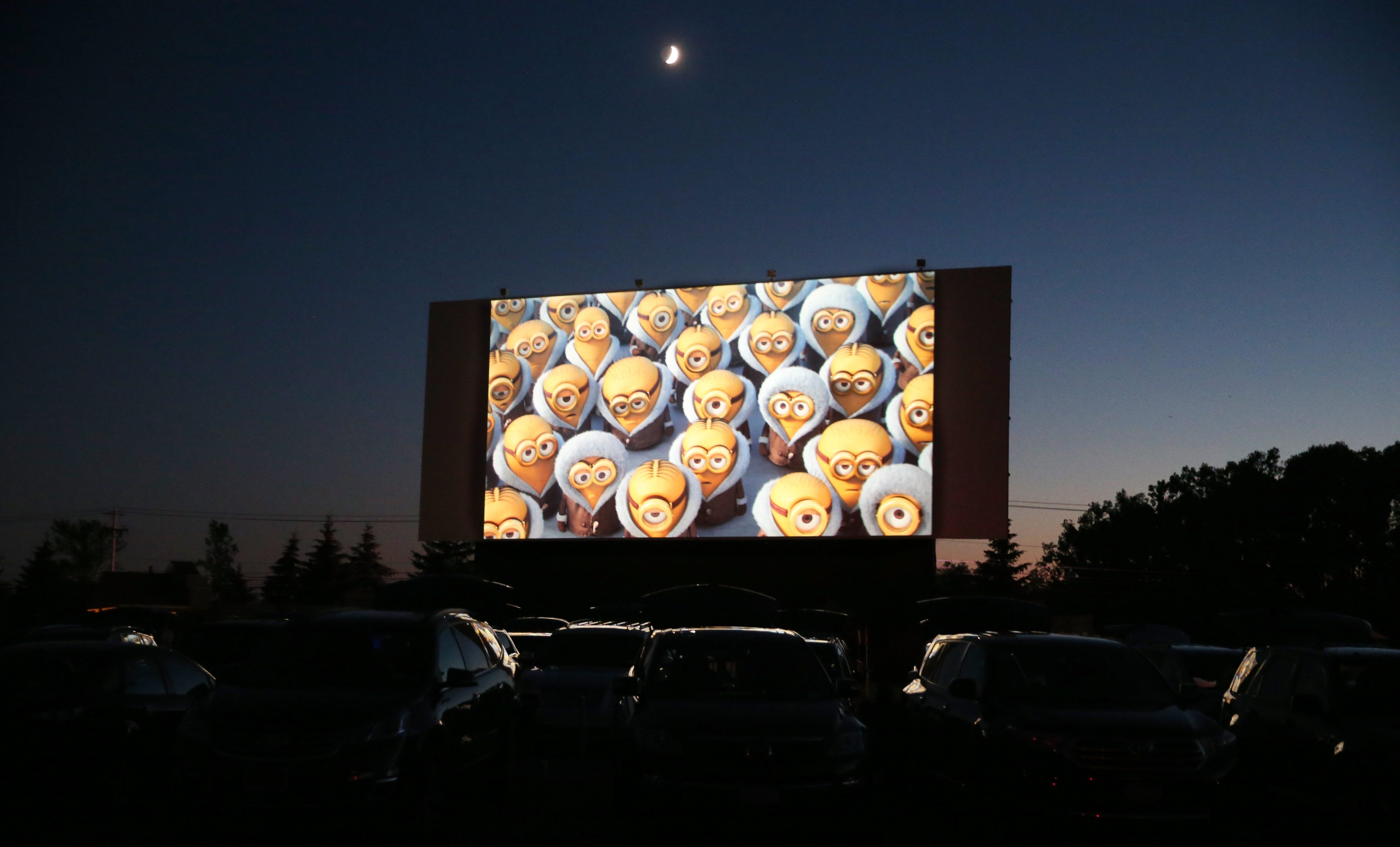 """Movie night: With three drive-ins to choose from, Western New Yorkers have a unique opportunity to pack up the car and catch a double feature. A recent trip to Lockport's Transit Drive-In found plenty of action on all four screens. 1.) The animated movie """"The Minions"""" was showing on the main screen. 2.) Samantha Ocejo, 9, of Niagara Falls, maneuvers her popcorn under the butter machine in the retro snack bar. 3.) Christina Birt, 14, stands at attention as the national anthem is played before the movie. 4.) Sitting next to their Trans-Am, two patrons settle in for the 1977 car chase classic """"Smokey and the Bandit,"""" which features Burt Reynolds driving a Trans-Am. 5.) Children ride the vintage merry-go-round before the movie. Randall Shortridge, who was at the drive-in with his family, said the ride appears to be the same one he rode as a child. 6.) The neon sign lists the night's lineup. 7.) Crystan Soule and Marc Ducharme of North Tonawanda wait in line for snacks at the Starlite snack bar, named after an old Town of Niagara drive in. 8.) Ann Marie Simmon, left and Audrey Ash relax in lawn chairs to enjoy """"Smokey,"""" Ash's favorite movie."""