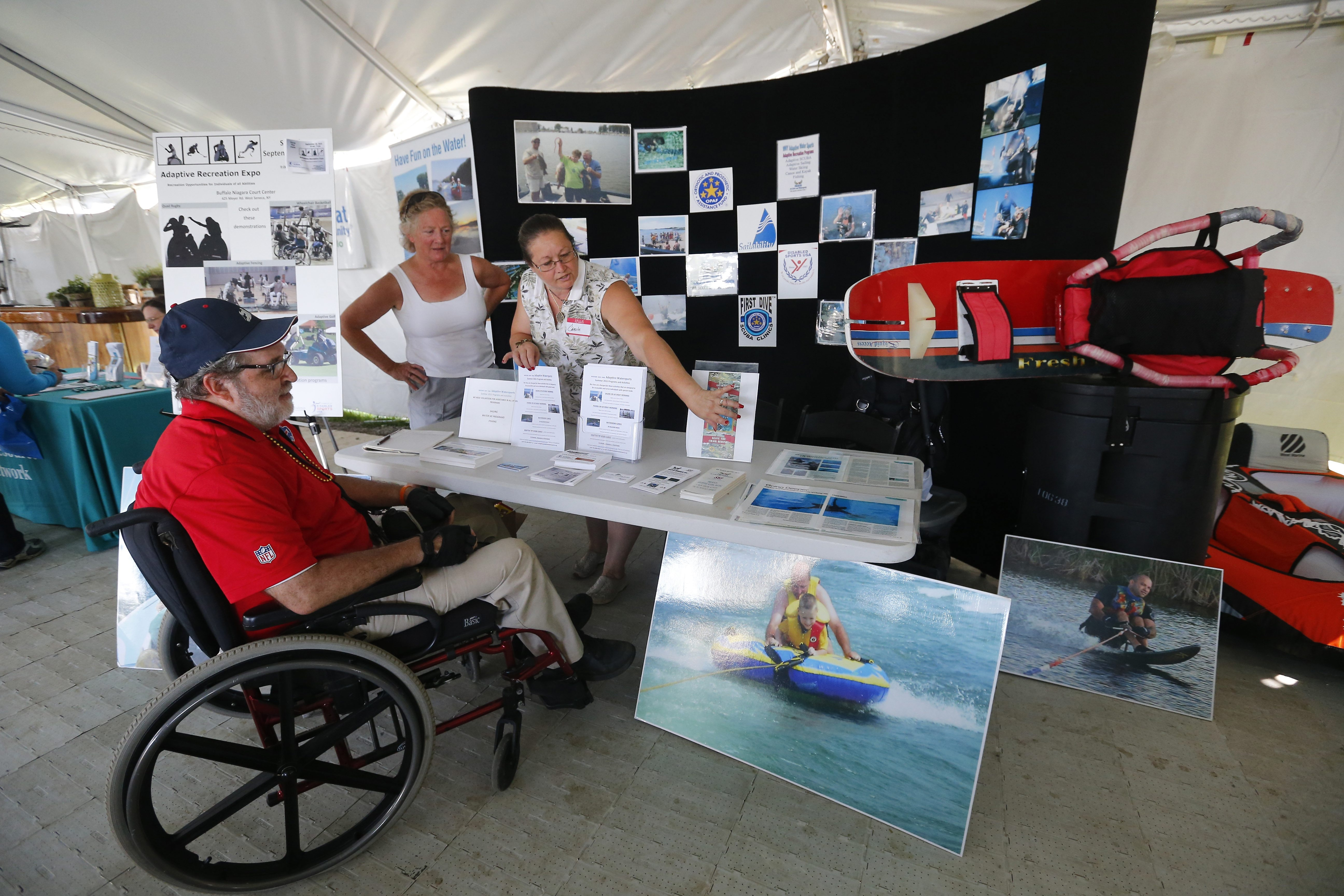 Thomas Hagerty, who has had multiple sclerosis for more than 30 years, visits booth of WNY Adaptive Water Sports, where Carol Reis, center, and Carole Anderson explain the variety of programs offered, during the 25th-anniversary celebration of the Americans with Disabilities Act on Sunday at Canalside.