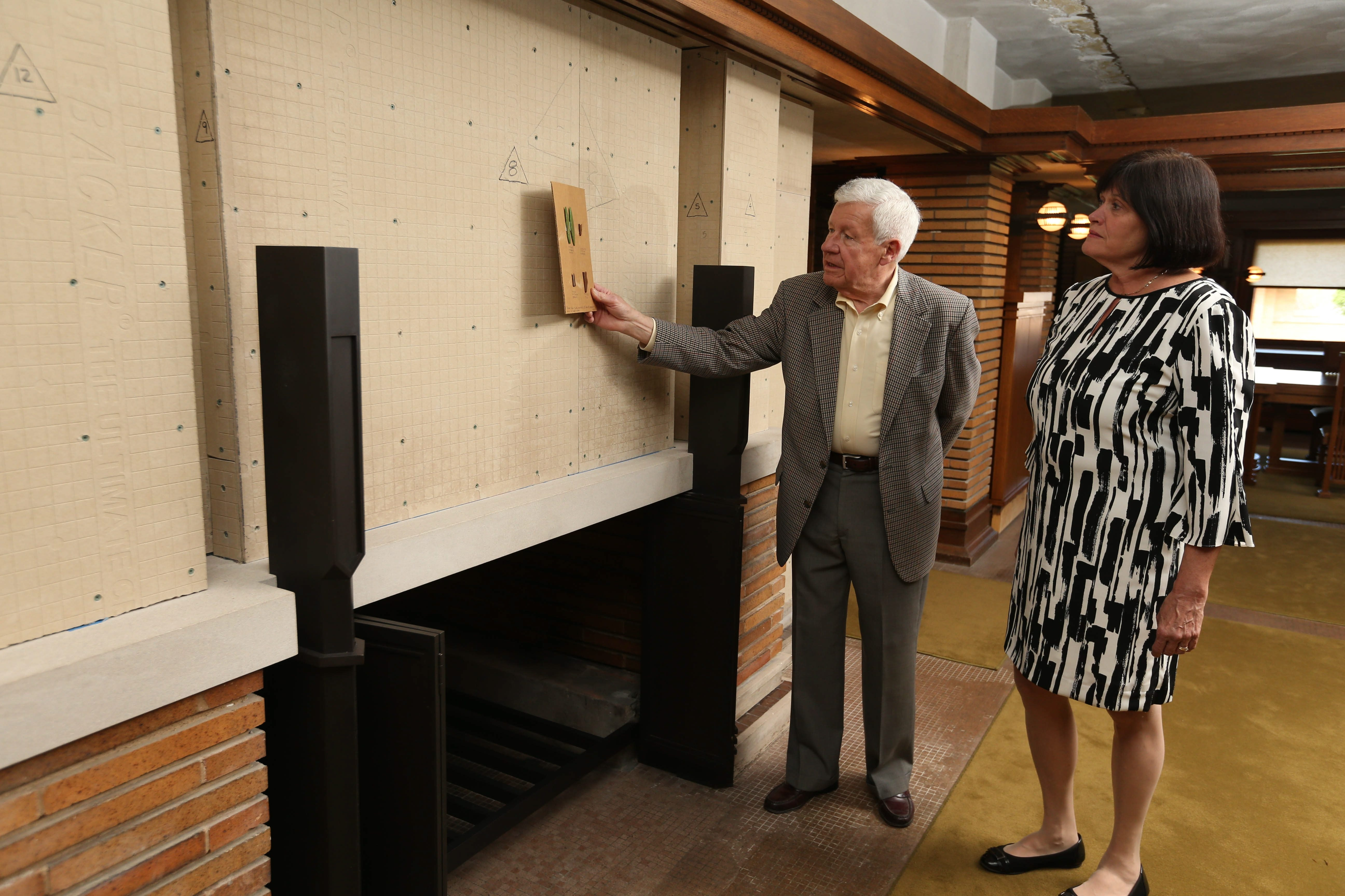 Mary Roberts, executive director of the Darwin D. Martin House, and Ted Lownie, restoration architect from HHL Architects, look at some of the original glass mosaic pieces that are being reproduced for the restoration of one of the fireplaces.