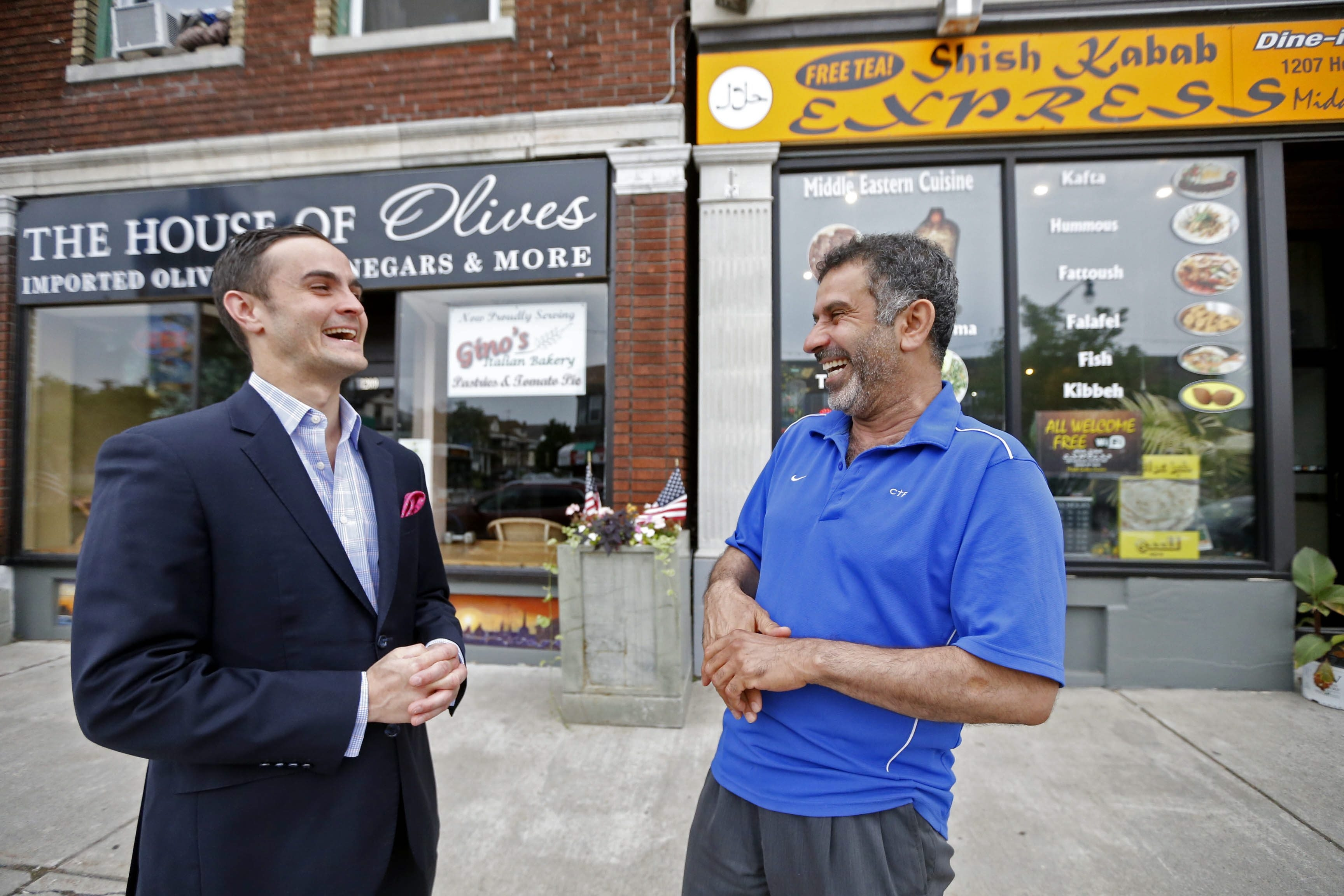 Tommy Lombardo Jr., left, of Ristorante Lombardo, and Adnan Abdulsaid, co-founder of Shish Kabab Express, share a laugh on the sidewalk of Hertel Avenue's Italian District.