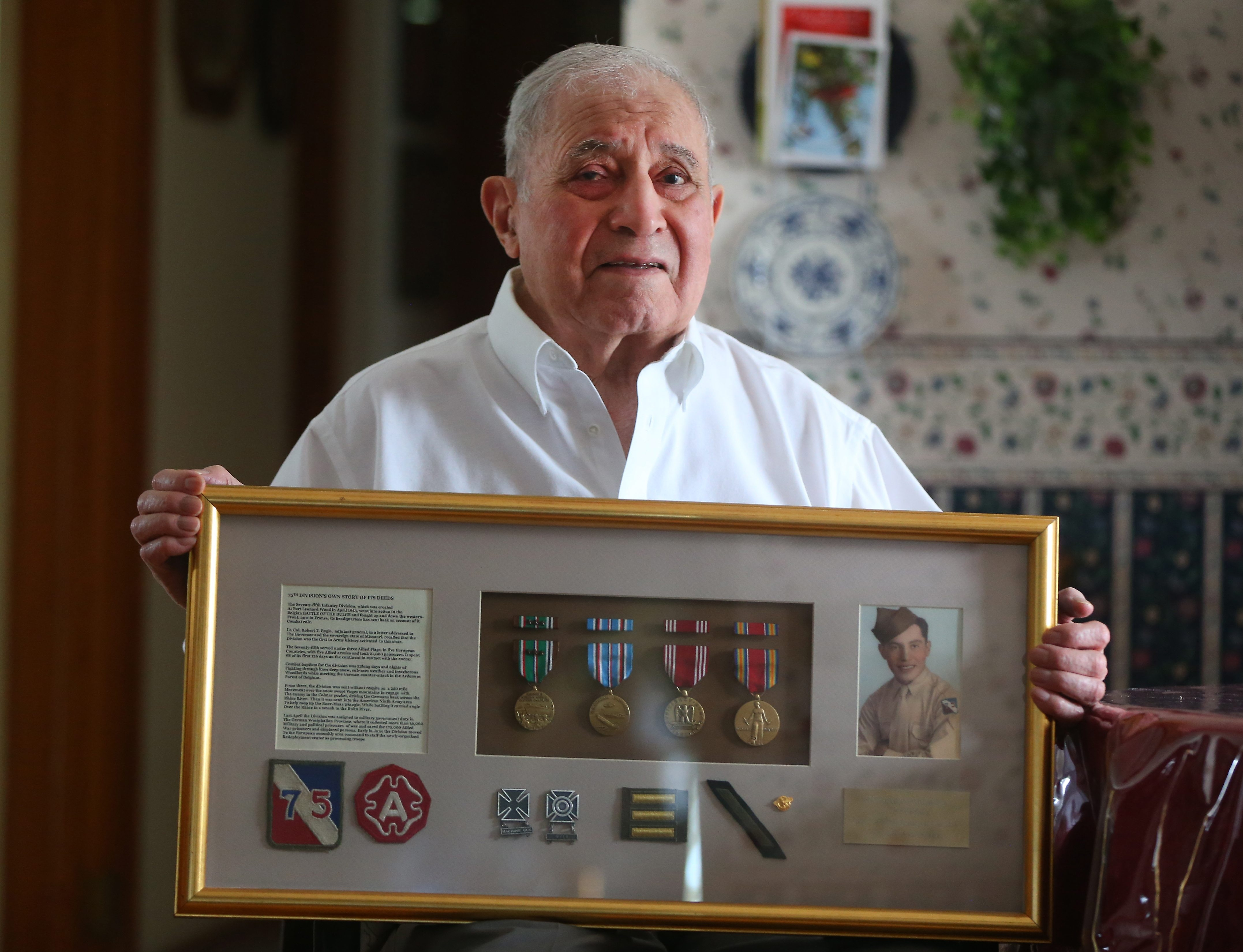 Ramon Romero shows medals, insignias and other WW II items that he displays in his home.