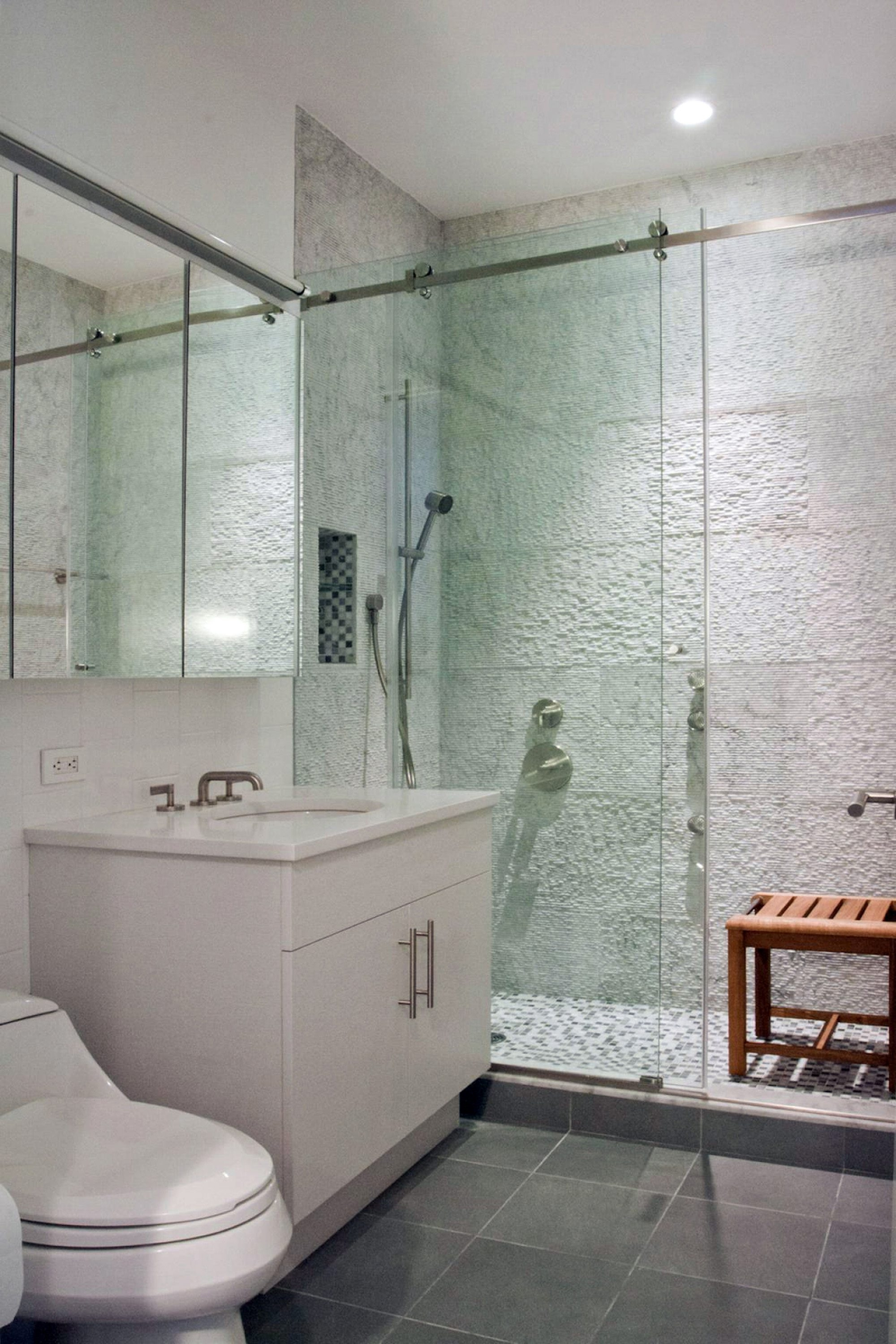 A wall of textured Carrara marble in a glass-enclosed shower with a stone mosaic tiled floor.  (Anjie Cho)