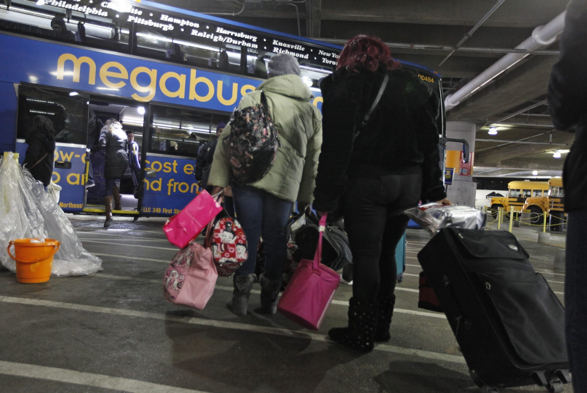 Passengers wait to board a Megabus at a bus terminal in Washington, D.C., on Jan. 4, 2013. Megabus is expanding its reserved seating program from 10 seats per bus to 20 seats.