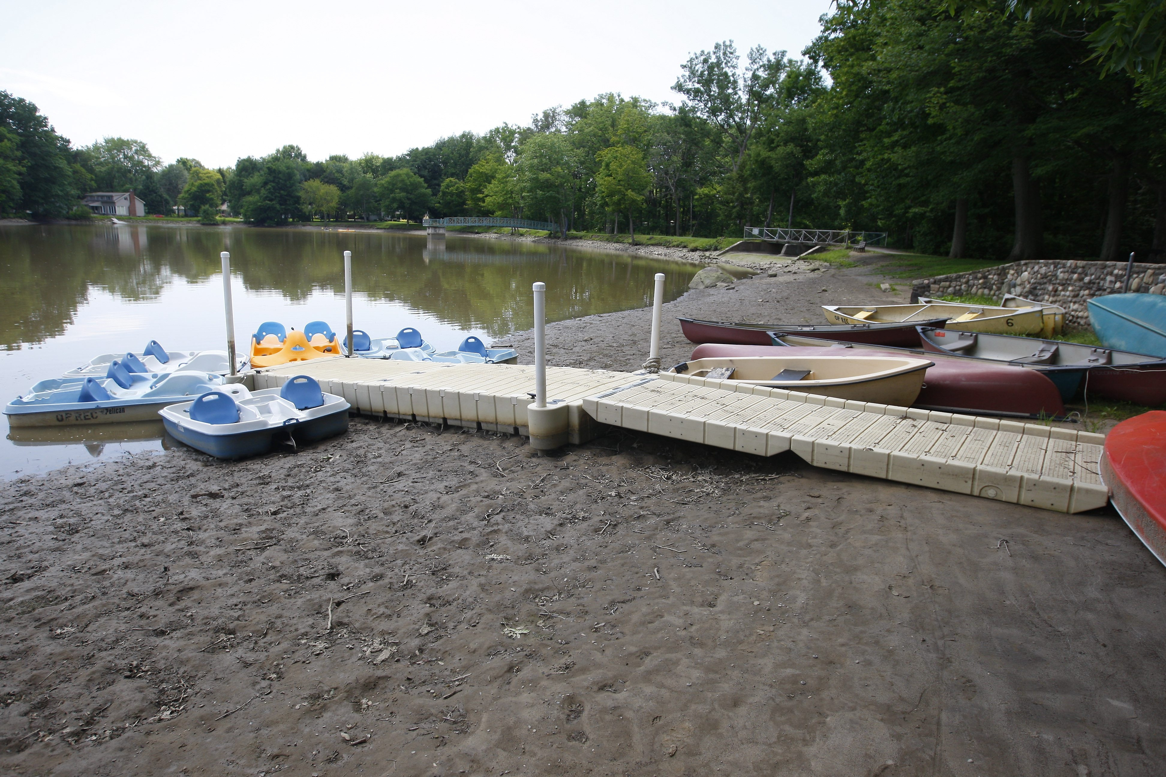 A dock and boats that are usually on the water rest on sand at Orchard Park's Green Lake. A dam left open drained more water than expected.