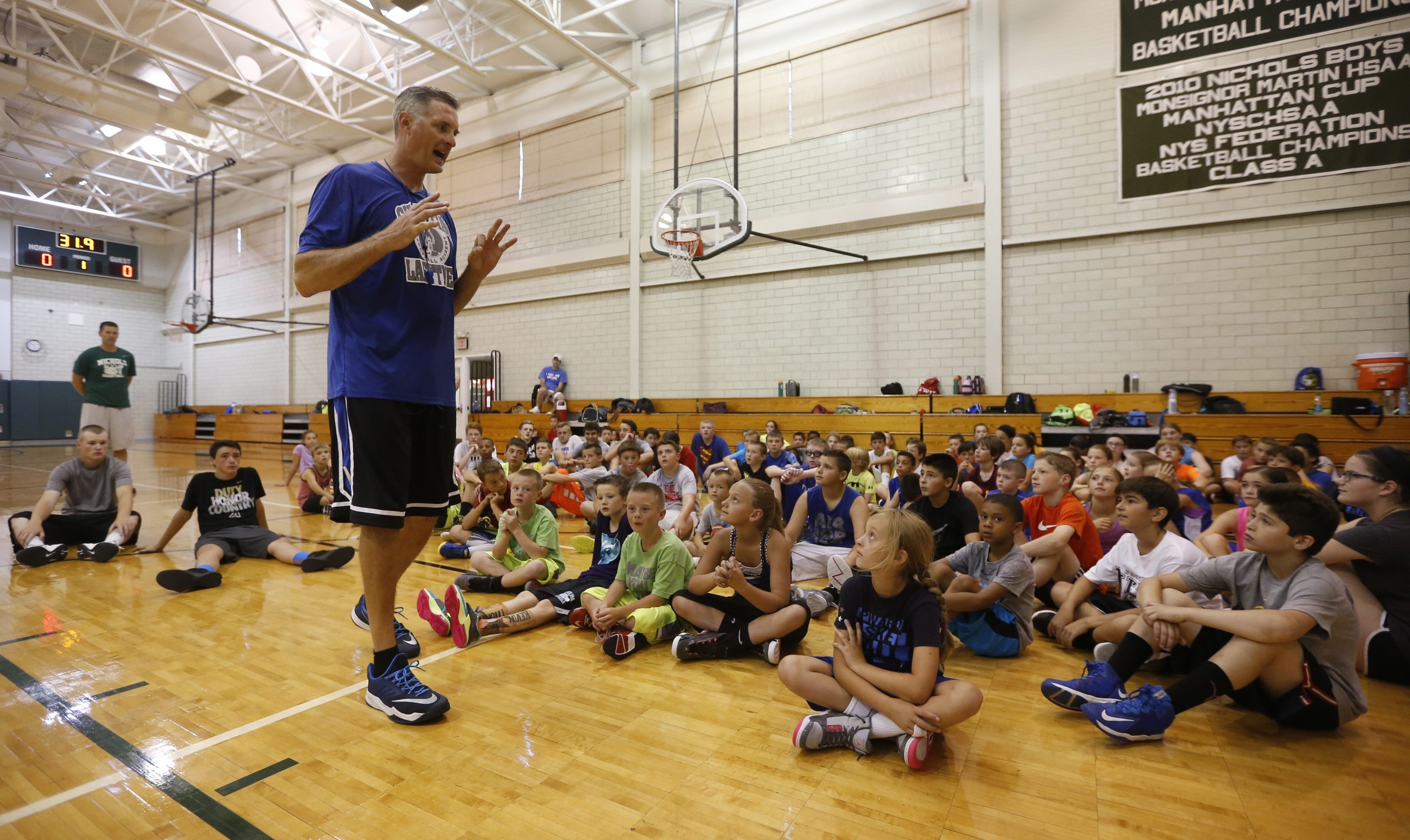 An attentive audience listens as Christian Laettner talks about fundamentals to the campers at his basketball academy at Nichols School.