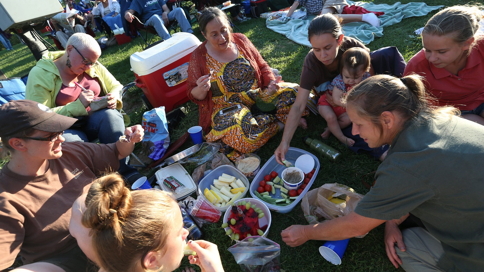 Part of the experience of Shakespeare in the Park at Delaware Park is bringing a picnic to enjoy before and during the performance. Clockwise from bottom left are Kerturah Stevens, Vicki Barr, Kim Zittel, Bonnie Barr, Alex Ash with daughter Hazel, 1, Jerusha Stevens and Janice Stevens, who is celebrating her birthday.  (Sharon Cantillon/Buffalo News)