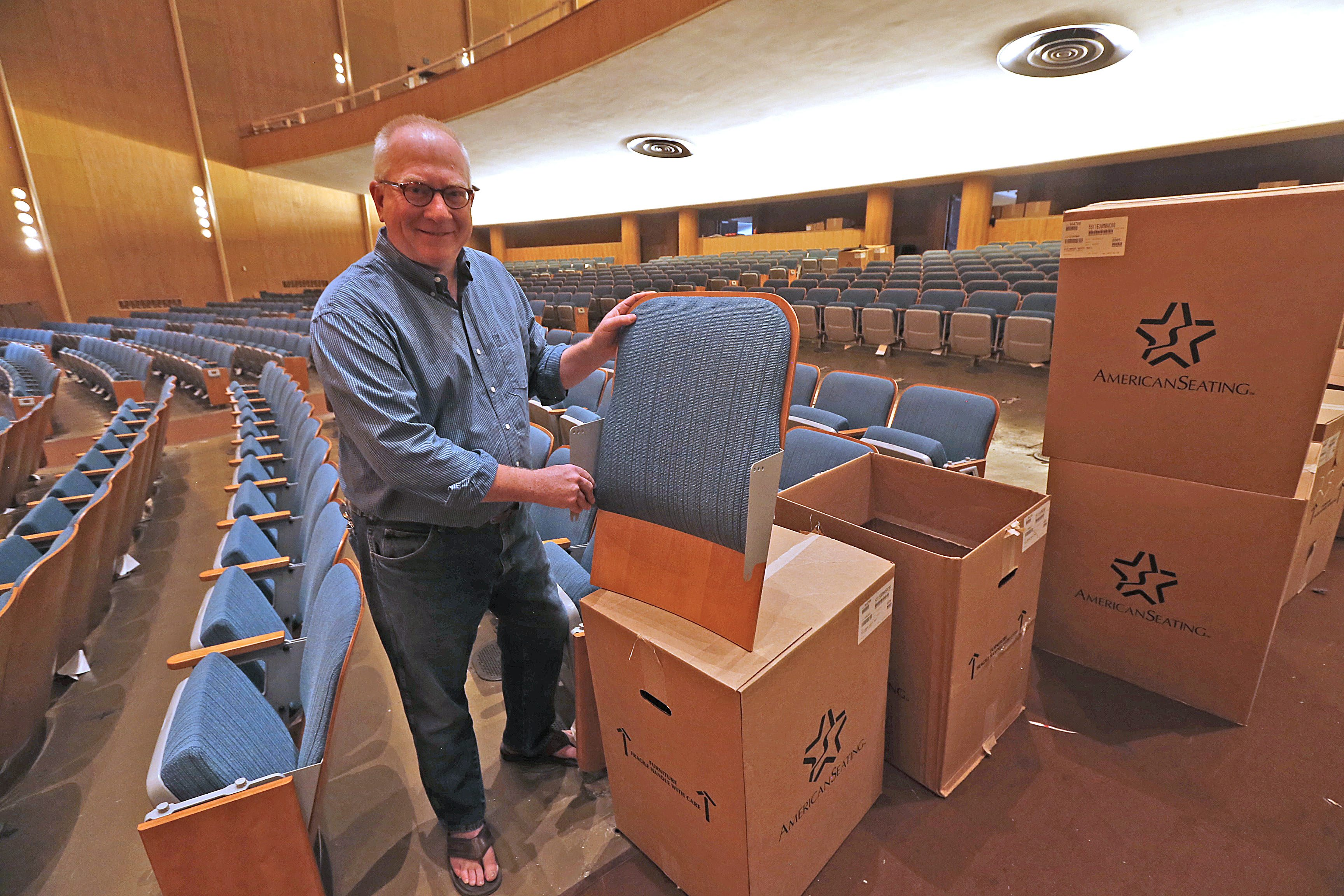 BPO Executive Director Daniel Hart shows off the back one of the new seats currently being installed at Kleinhans Music Hall.