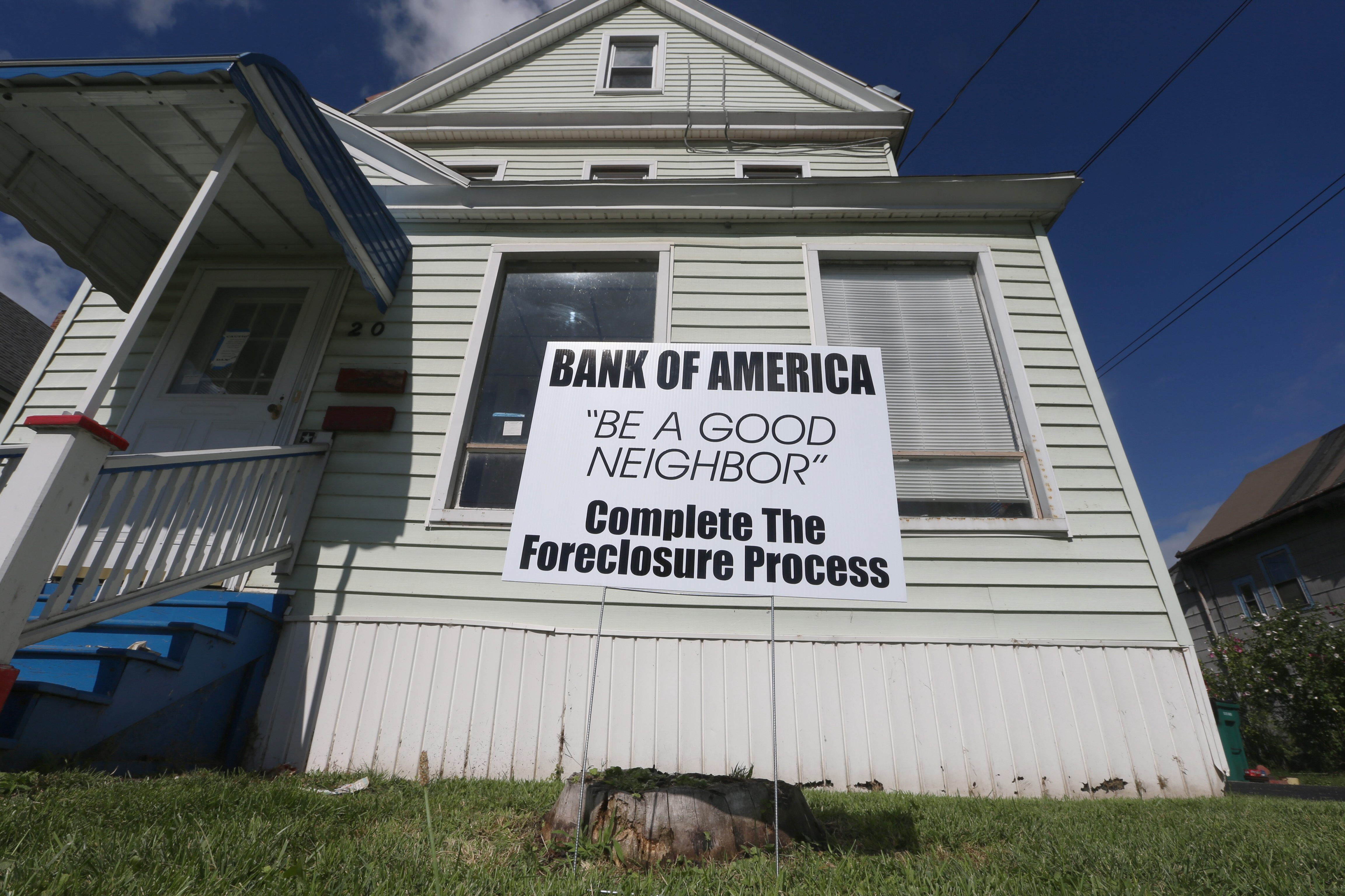 A sign draws attention to an empty home on Sidway Street in Buffalo, identifying the bank that initiated foreclosure in 2010. The property owner died in 2007, and the home has been vacant since.