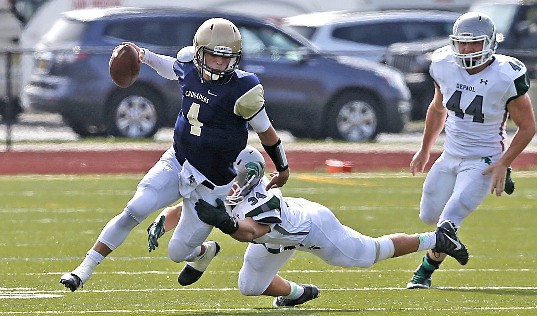 Canisius QB Tyler Stranahan slips away from defender Vinny DePalma of DePaul Catholic during Saturday's game in West Seneca.