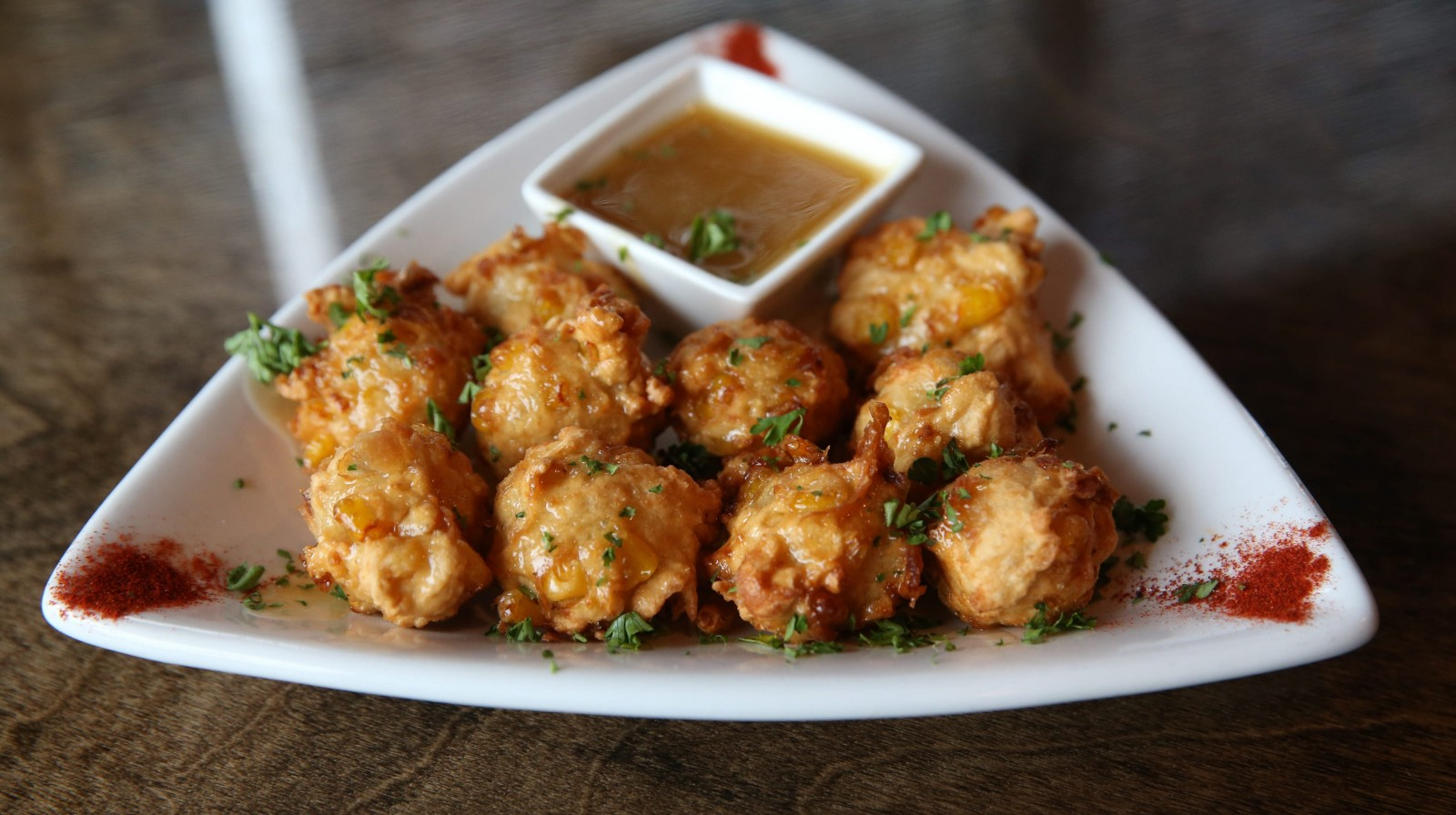 The corn fritters at the Griffon Gastropub in Clarence are spoonfuls of fresh sweet corn-filled batter, flash-fried and served with Vermont maple butter. (Sharon Cantillon/Buffalo News file photo)
