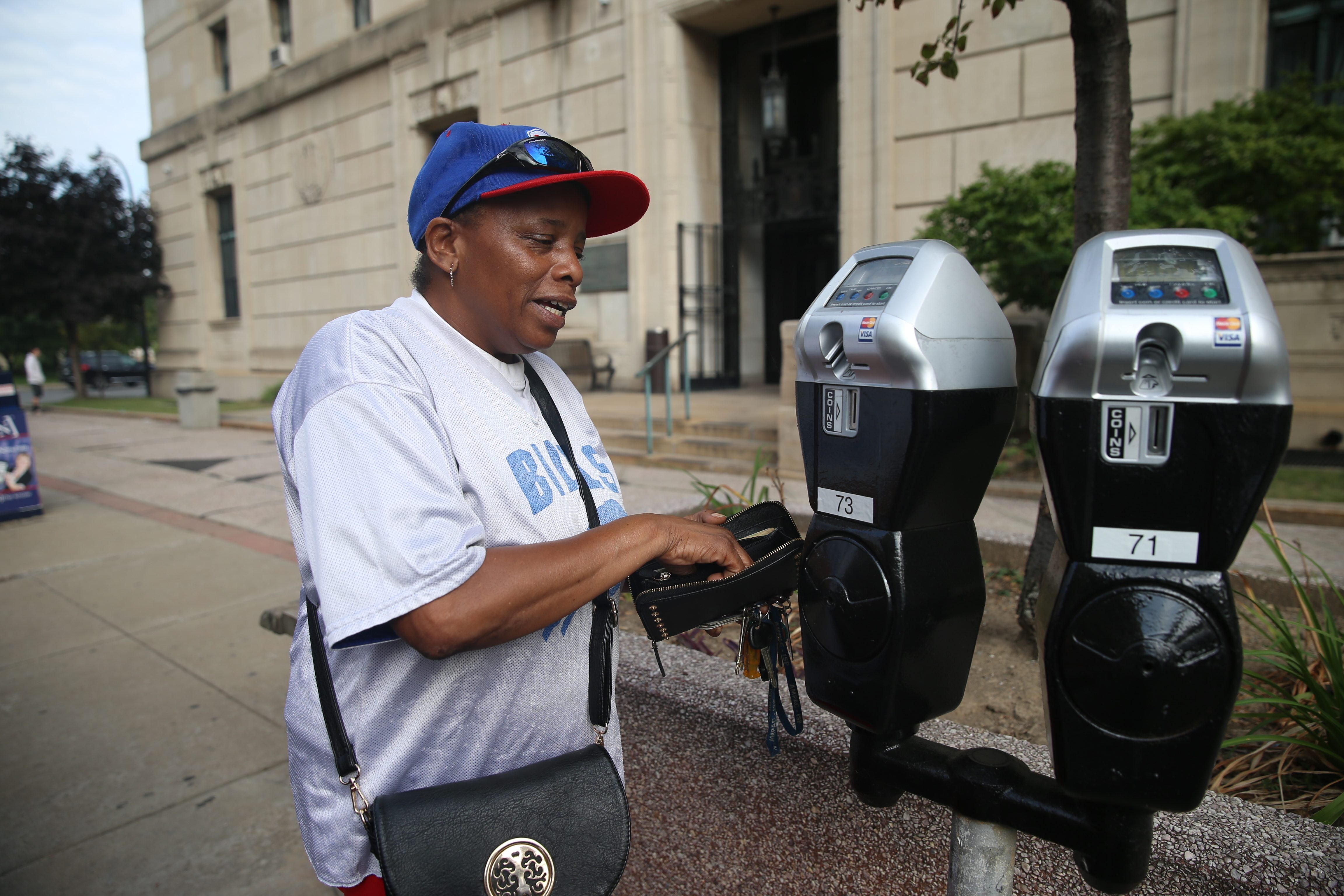 Patricia Douglas uses coins at new parking meters that take credit cards at Court Street in Buffalo.