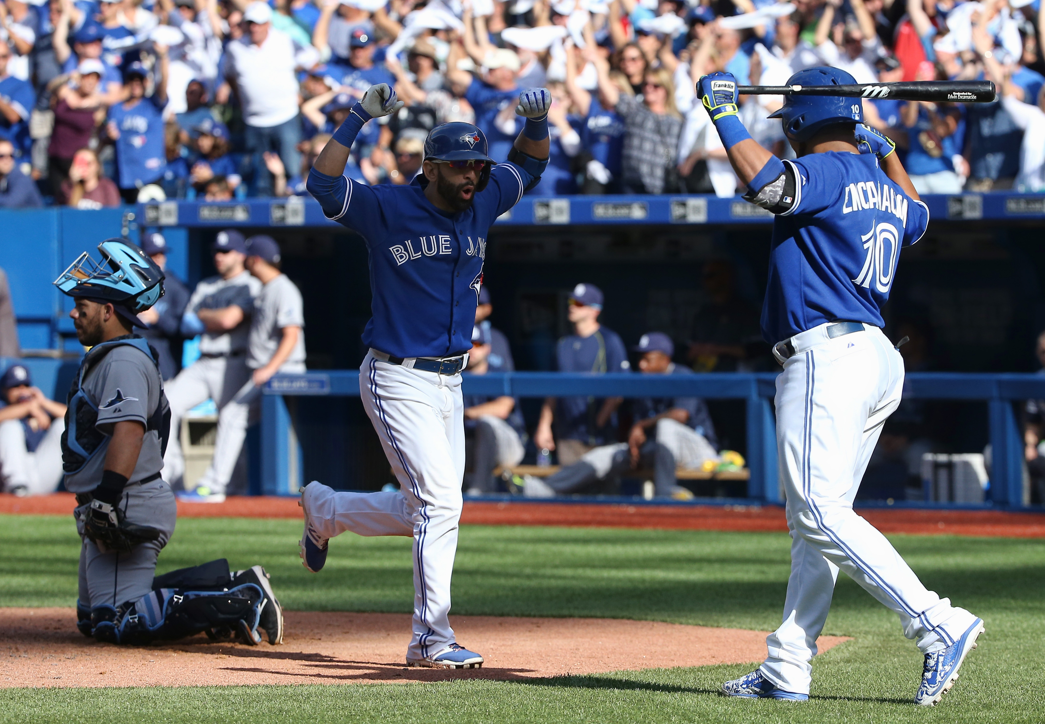 Toronto's Jose Bautista, center, is congratulated by Edwin Encarnacion after hitting a home run against the Tampa Bay Rays on Saturday. The Jays won, 10-8.
